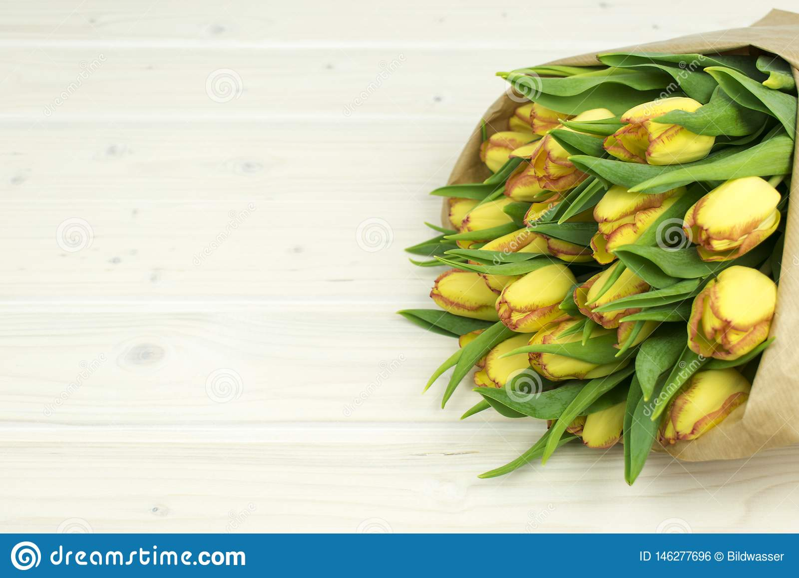 De bos van gele tulpen op een houten lijst wraped in document