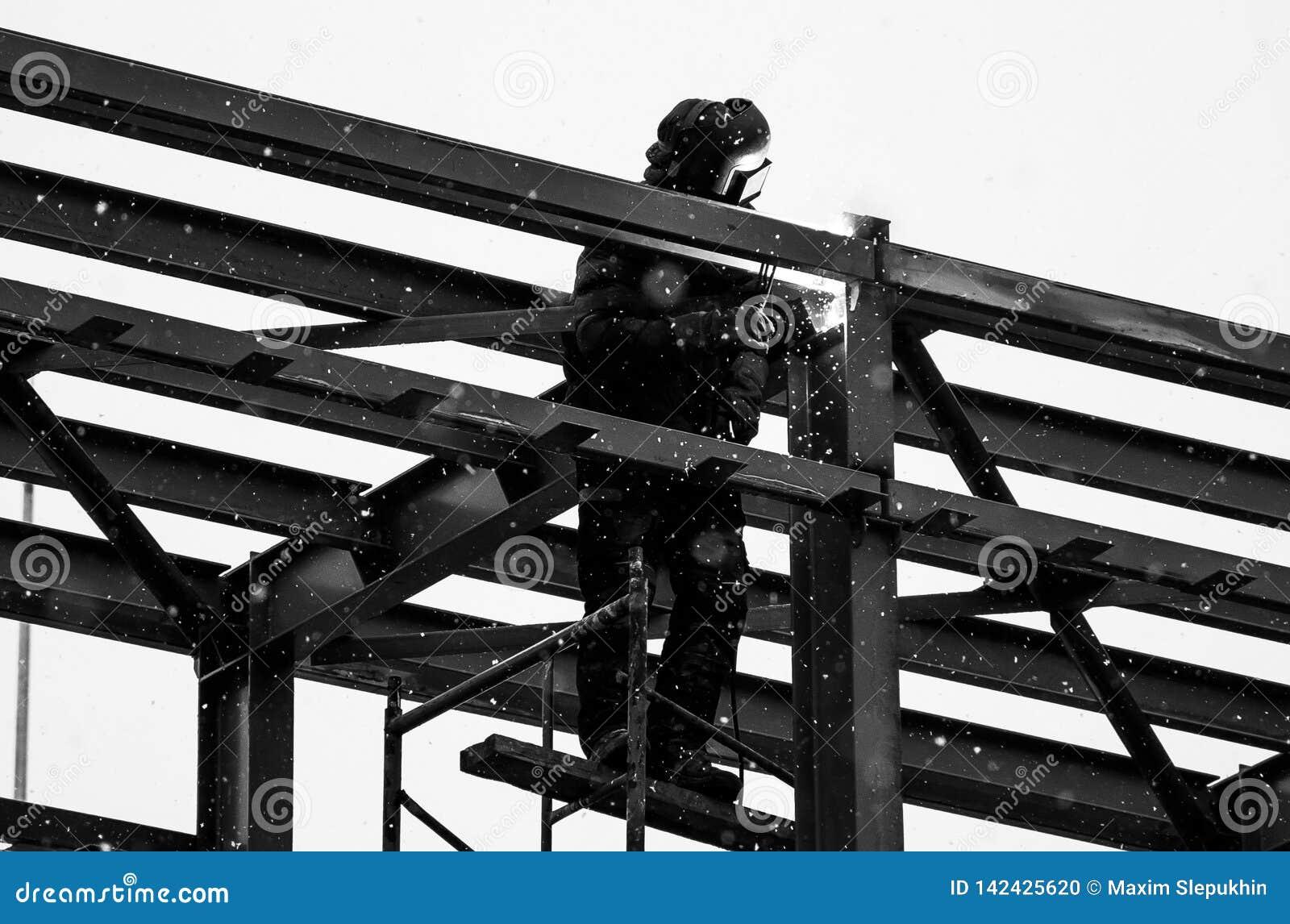 De Bouwer werkt bij sunsetblack en witte foto van een gemaskeerde lasser die bij hoogte werken