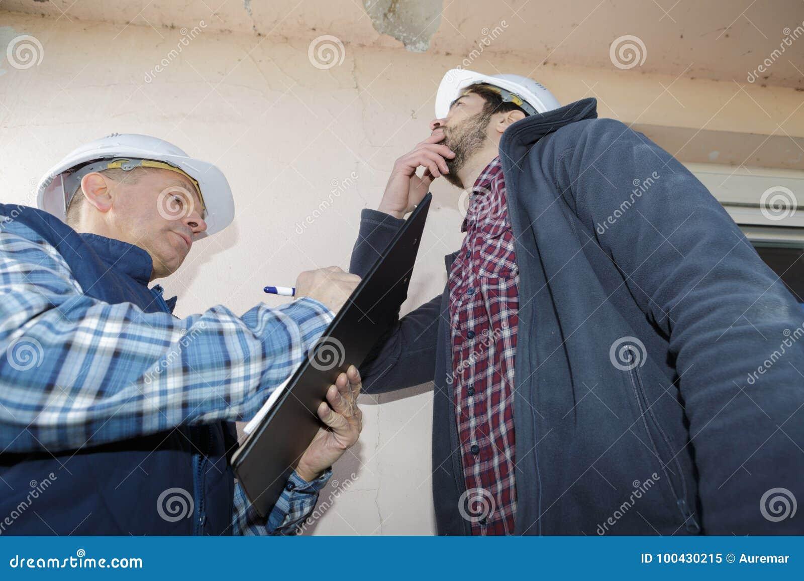 De bouwers die schil bekijken schilderen op binnenlands plafond