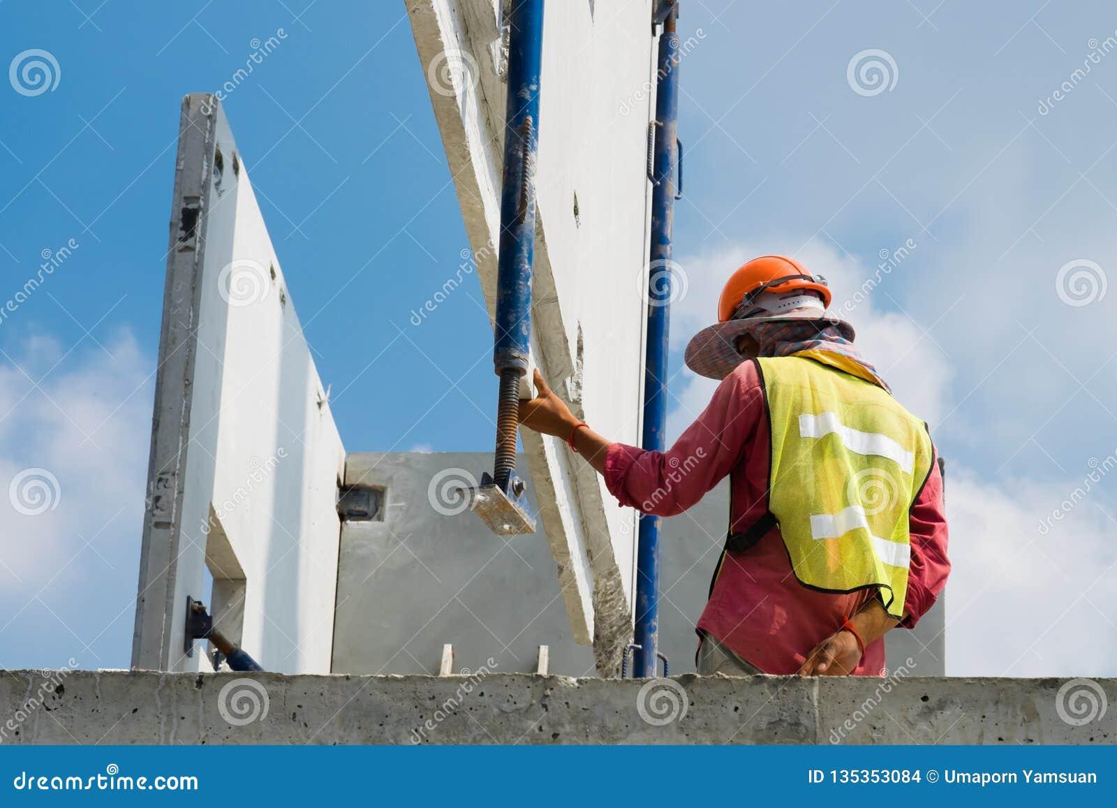 De bouwvakker installeert de geprefabriceerde concrete muur, de oranje veiligheidshelm en het groene vest