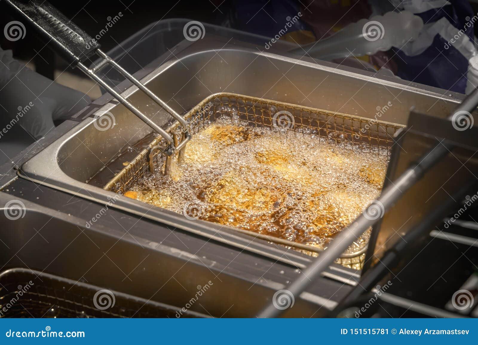 De braadpan van het netto voedsel wordt verminderd in kokende olie in een openluchtfast-food restaurant