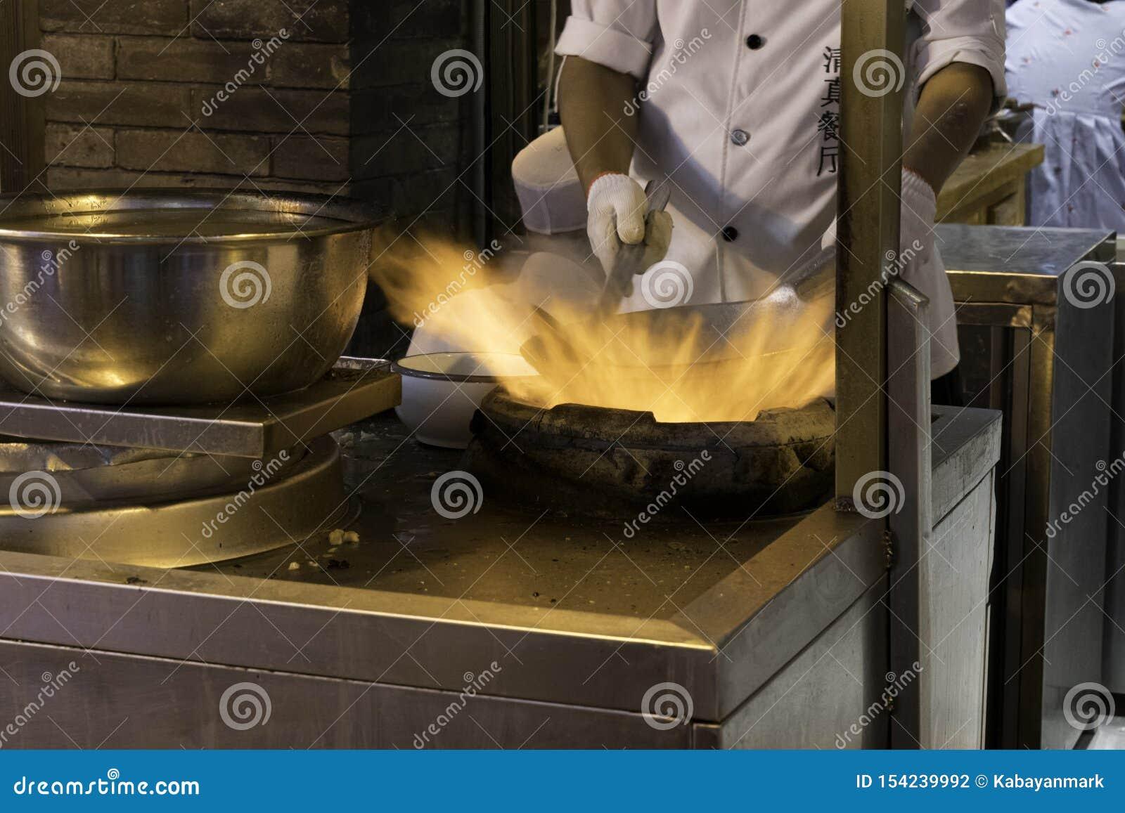 De brand en het Voedsel een Chinese chef-kok bereiden voedsel in een wok voor