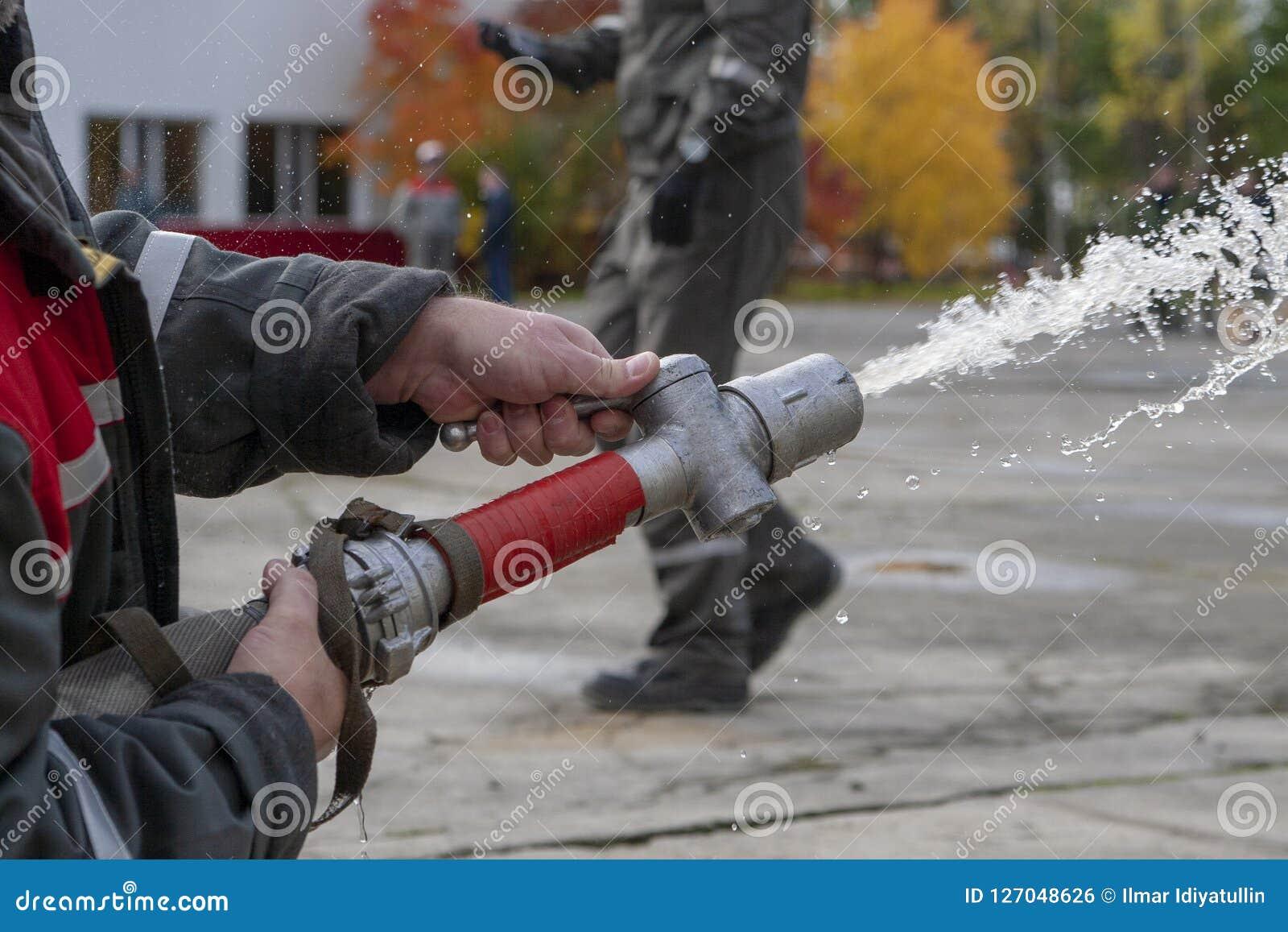 De brandbestrijders bespuiten water tijdens een opleidingsoefening