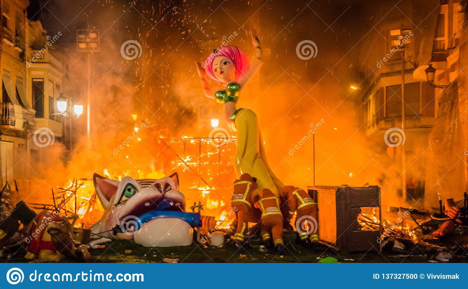 De brandmensen duwen een beeldhouwwerk in de brand tijdens Las Fallas in Valencia Spain