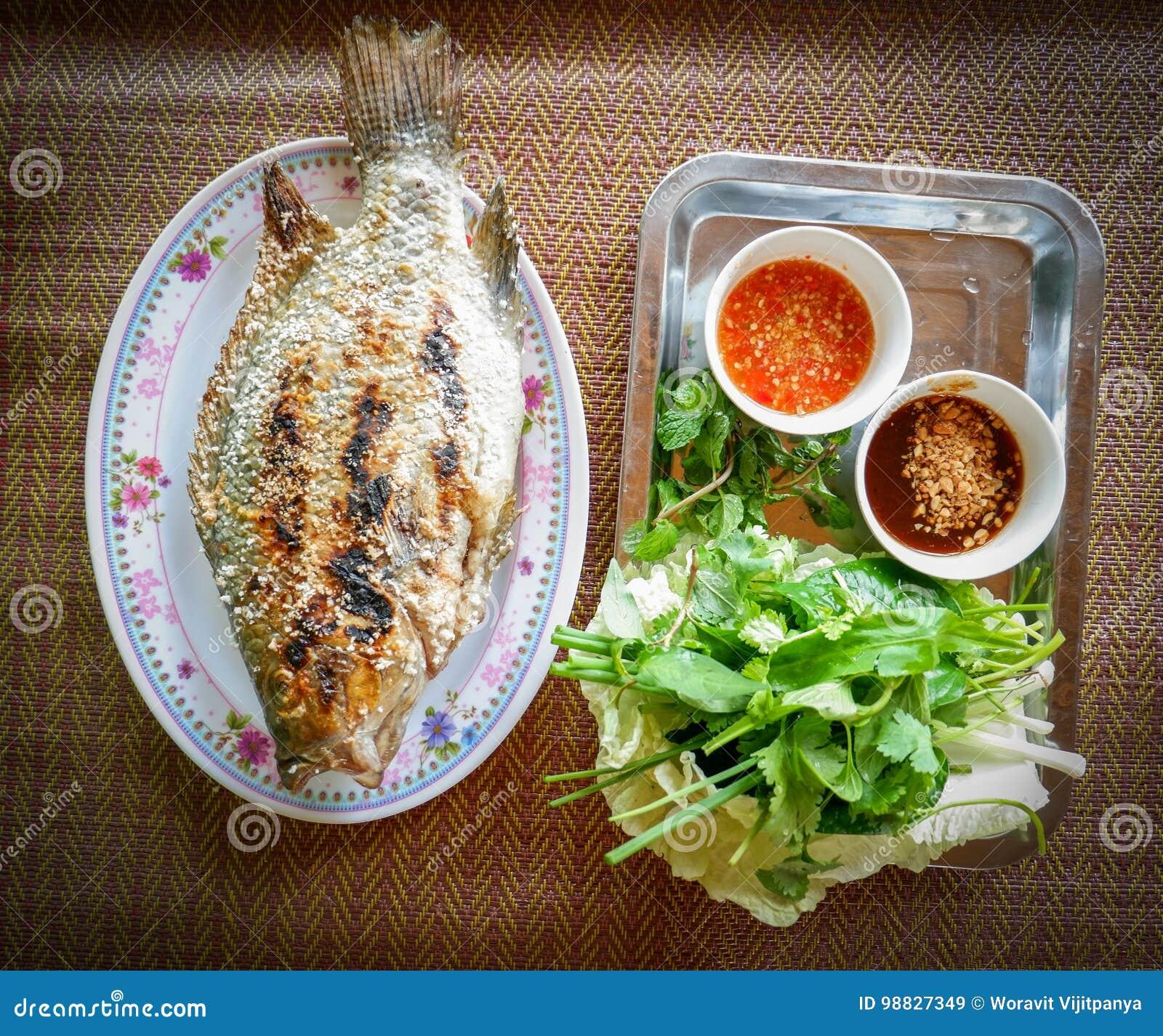 De Brandwond van grillvissen met saus en verse groenten