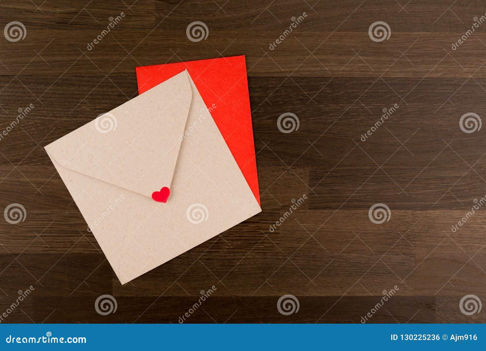 De brief van de envelopliefde Tow Envelopes Red en Bruin met een Hart op Houten Patroon