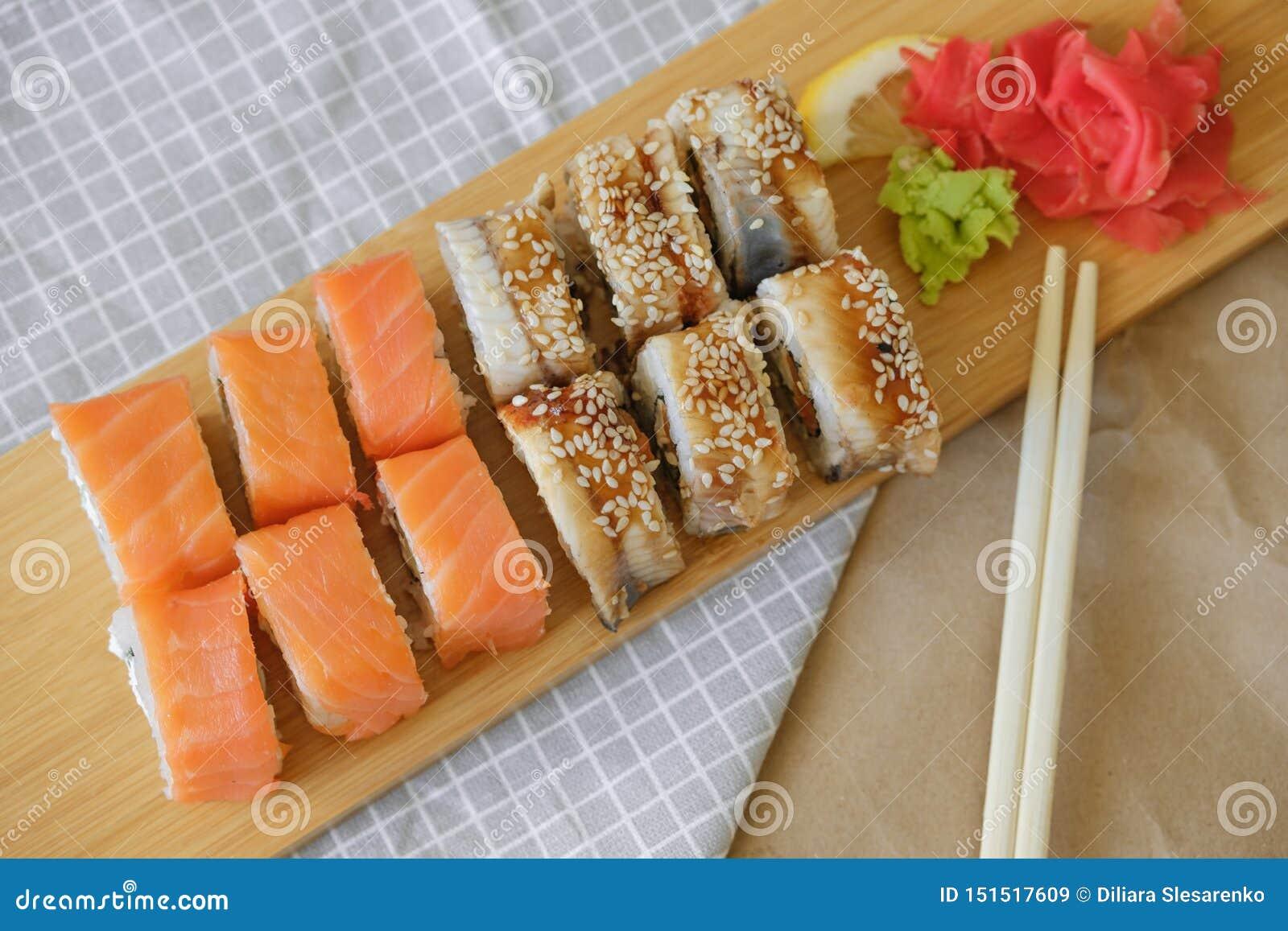 De broodjes met zalm en de broodjes met paling liggen op een houten plank