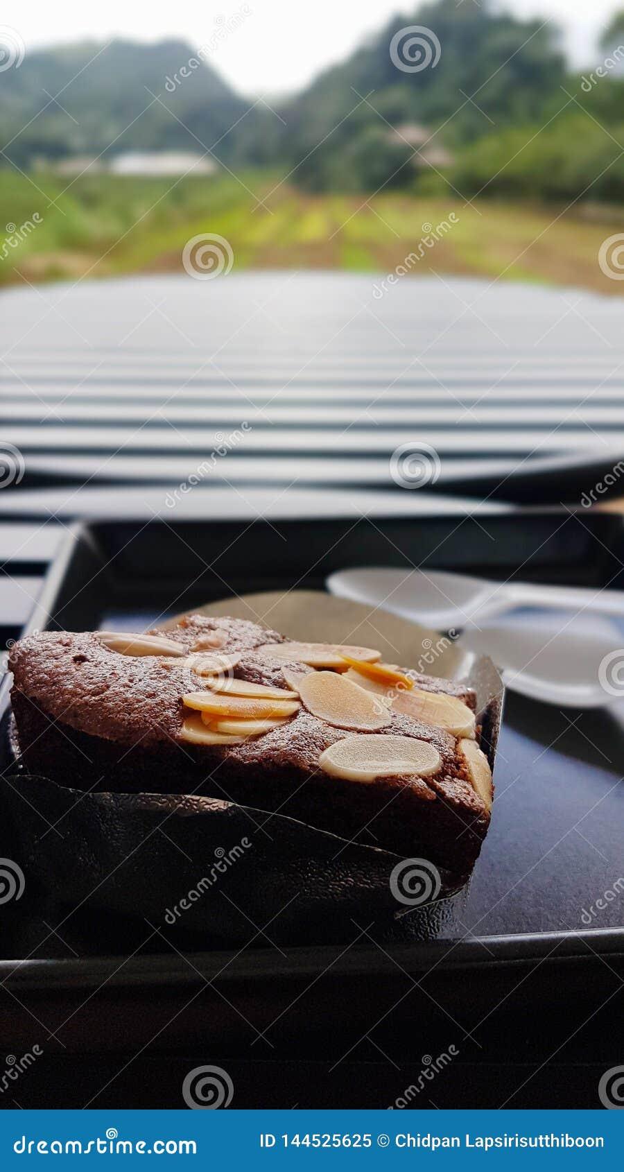 De brownie met amandel wordt glijdt binnen de Floyd-kop met een plastic lepel wordt geplaatst op een zwart plastic die dienblad o