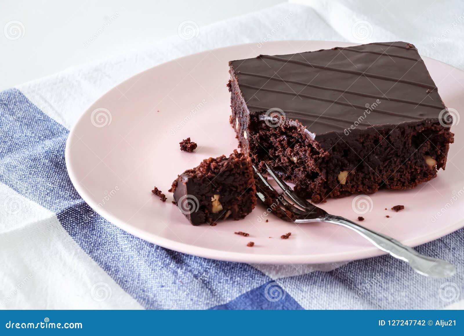 De browniecake van de chocoladeveganist met noten Roze plaat Lichte achtergrond