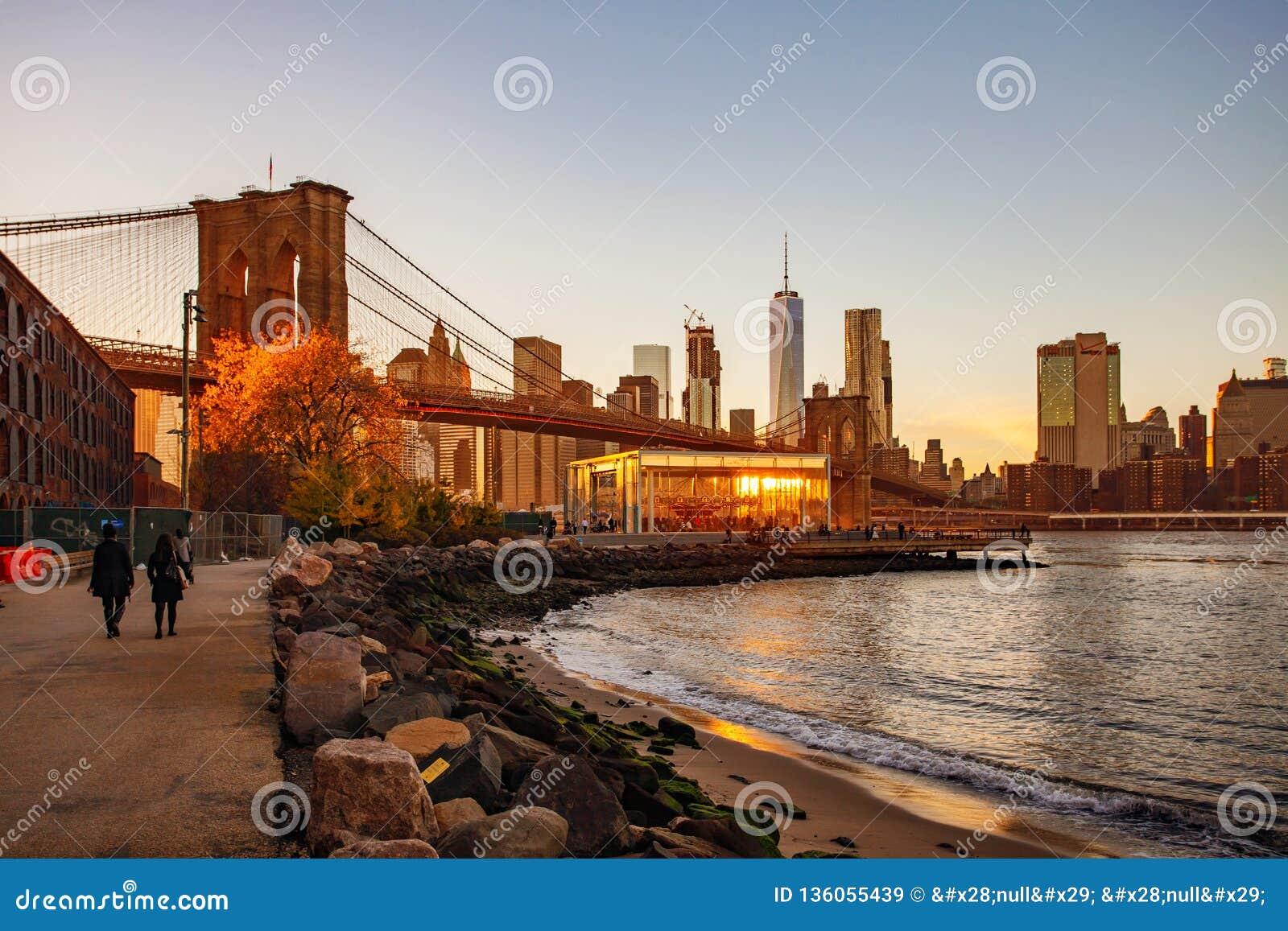 De Brug van Brooklyn bij zonsondergangmening bij de Stad van New York,