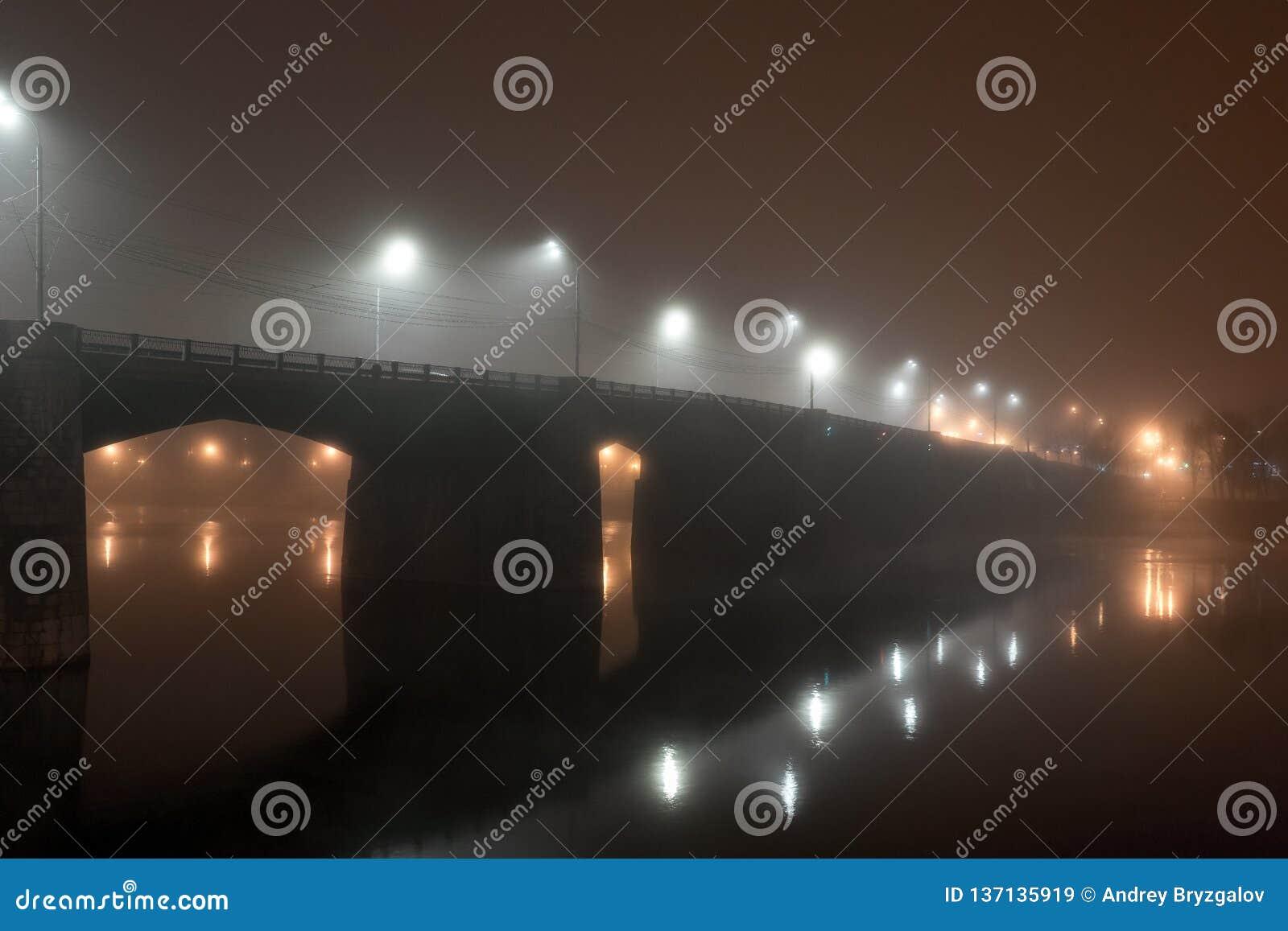 De brug van de stadsweg over rivier in dichte die mist bij nacht door lantaarns wordt verlicht