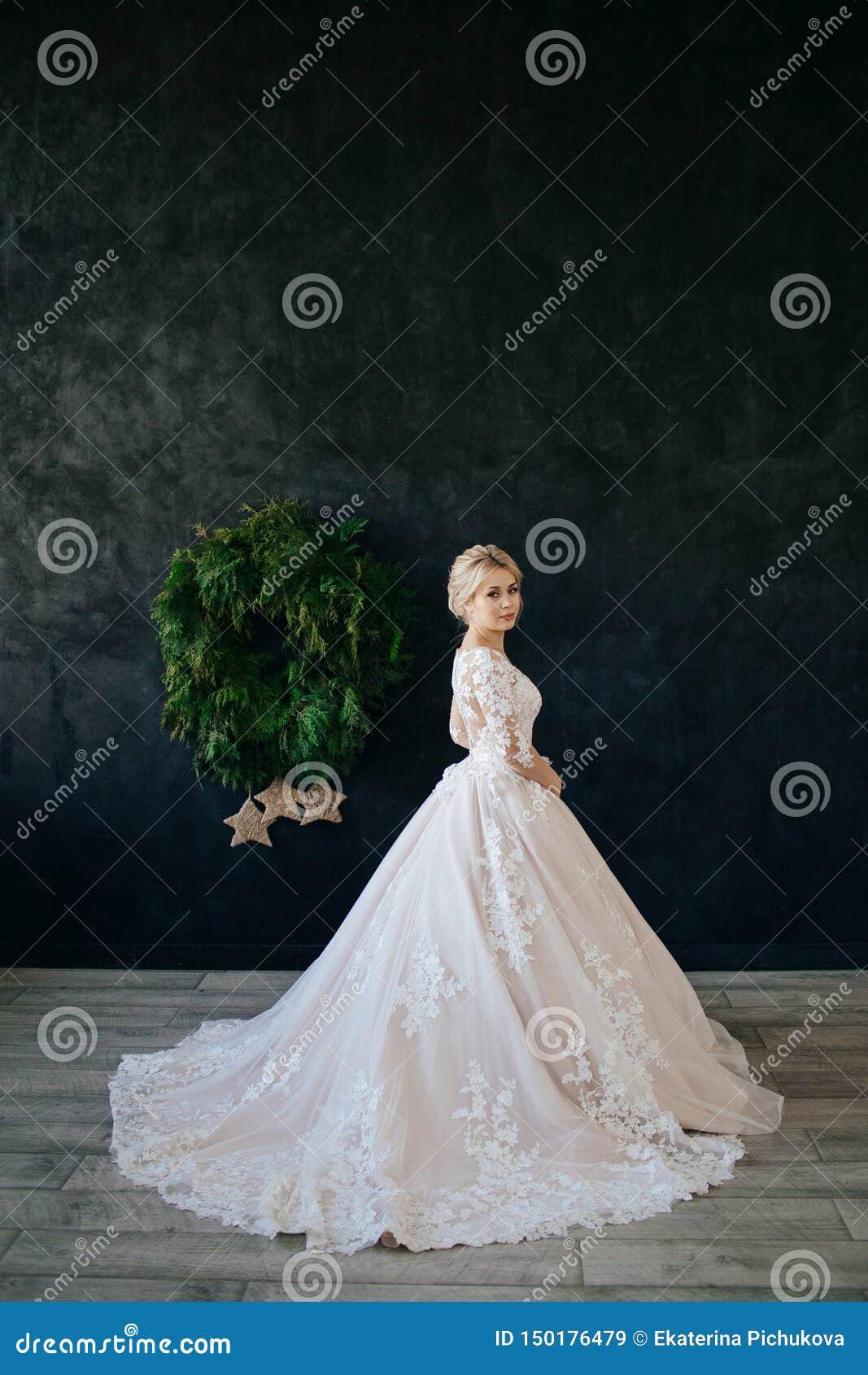 De bruid in een prachtige, witte, huwelijkskleding met een lange trein