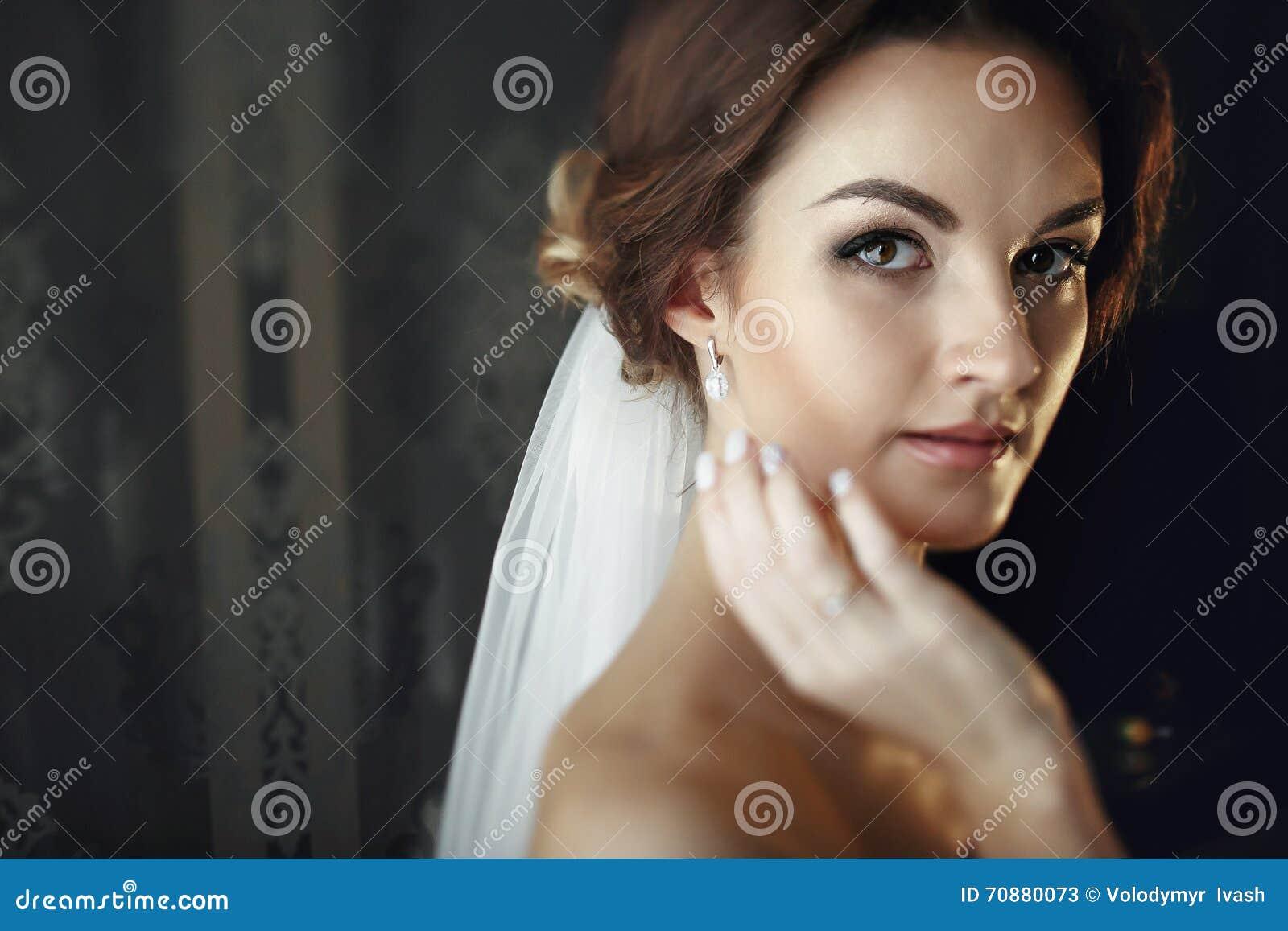 De bruid in een sluier raakt haar gezicht met hand