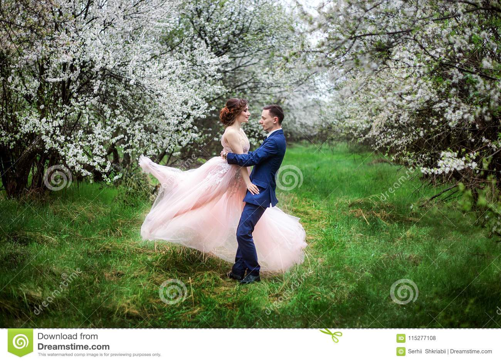 De bruid en de bruidegom in huwelijk kleden zich tegen de achtergrond van bloeiende tuinen