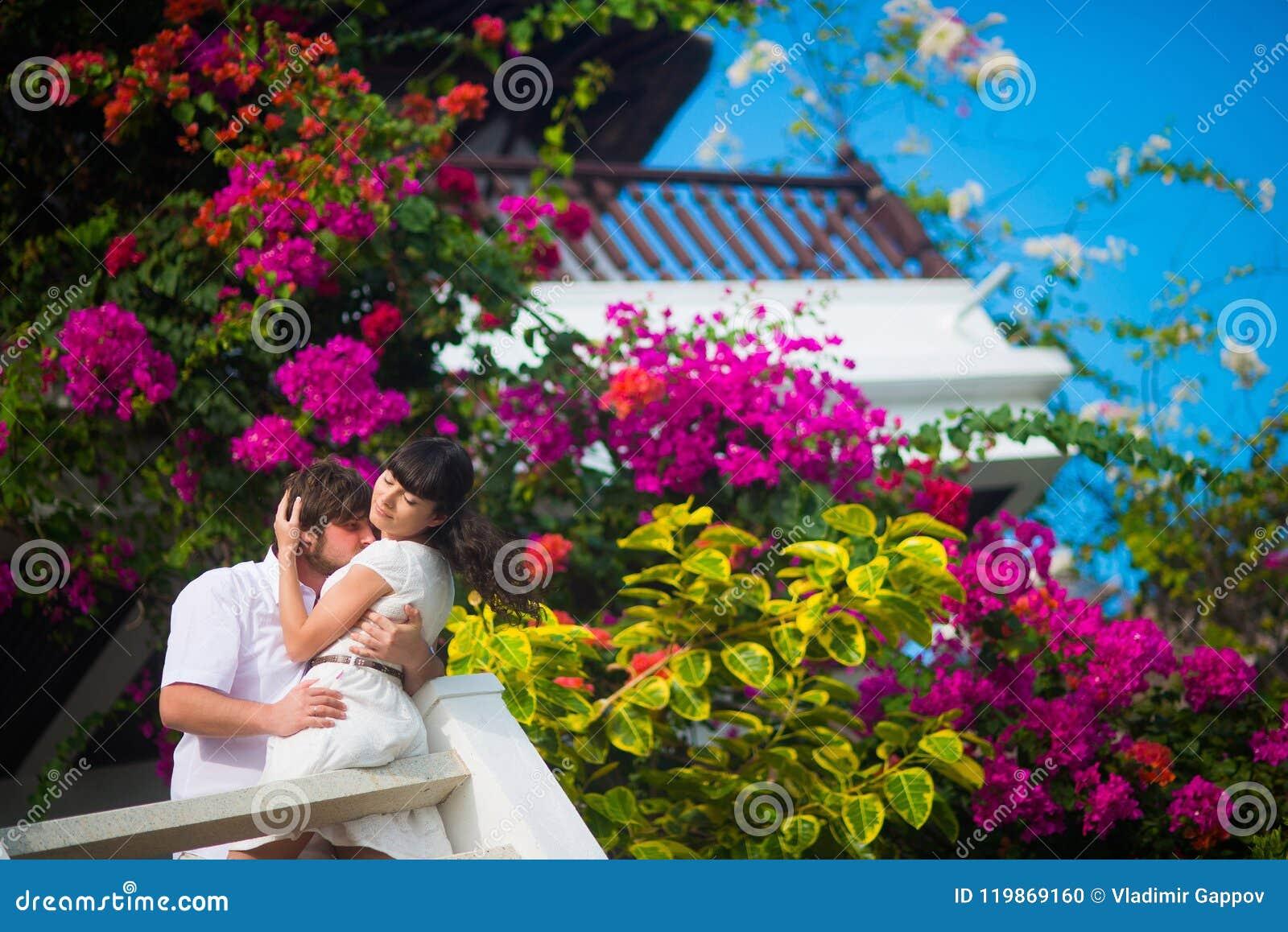 De bruid en de bruidegom omhelzen passionately op het balkon op een achtergrond van bloemen