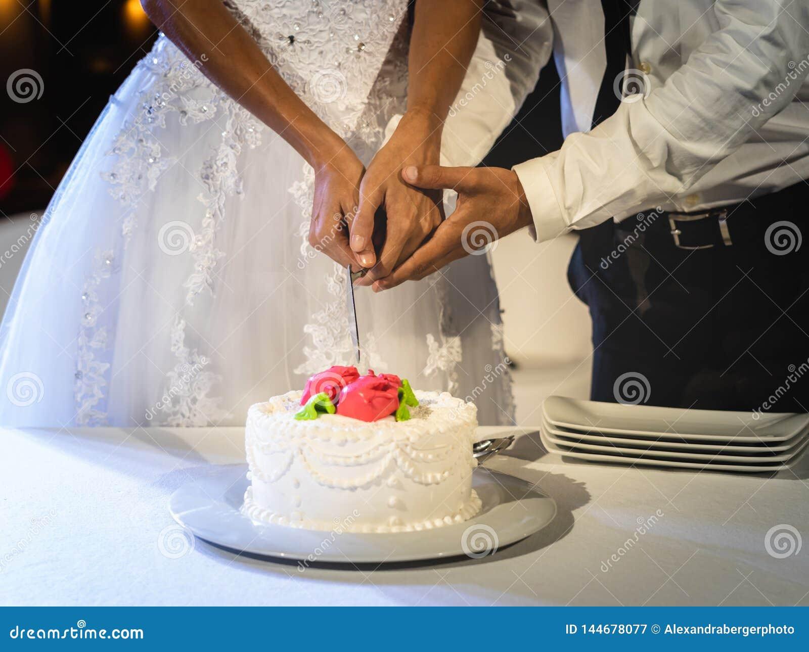 De bruid en de bruidegom snijden samen cake bij hun huwelijk
