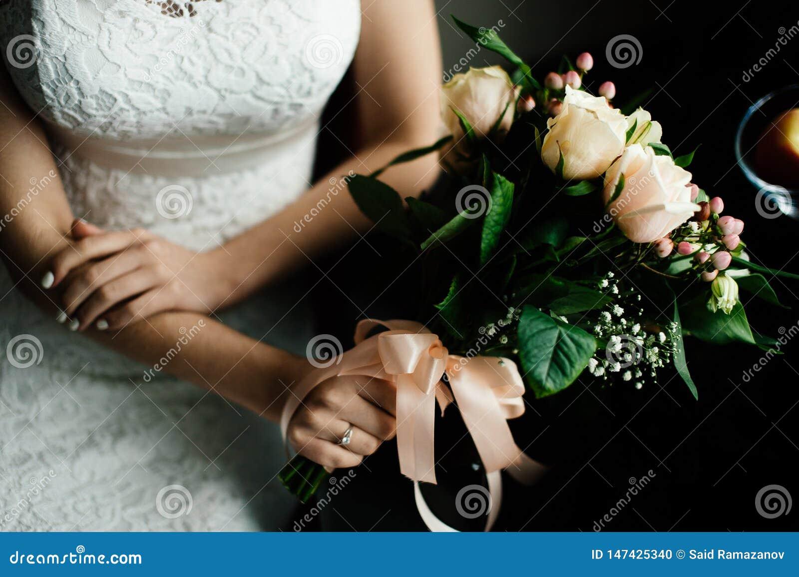 De bruid met een boeket van witte rozen zit door de lijst