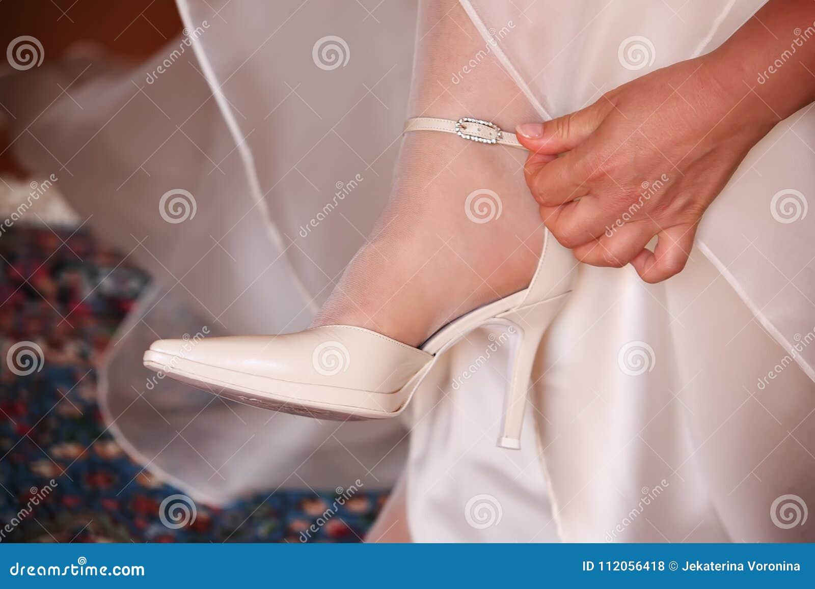 De bruid raakt de riem van schoenen