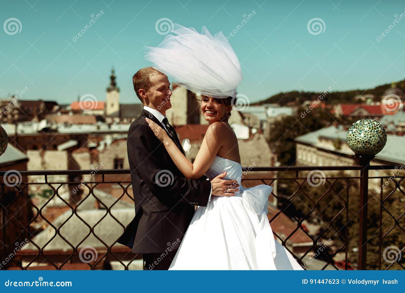 De bruidegom houdt een glimlachende bruid in zijn wapens op het dak in oud ci