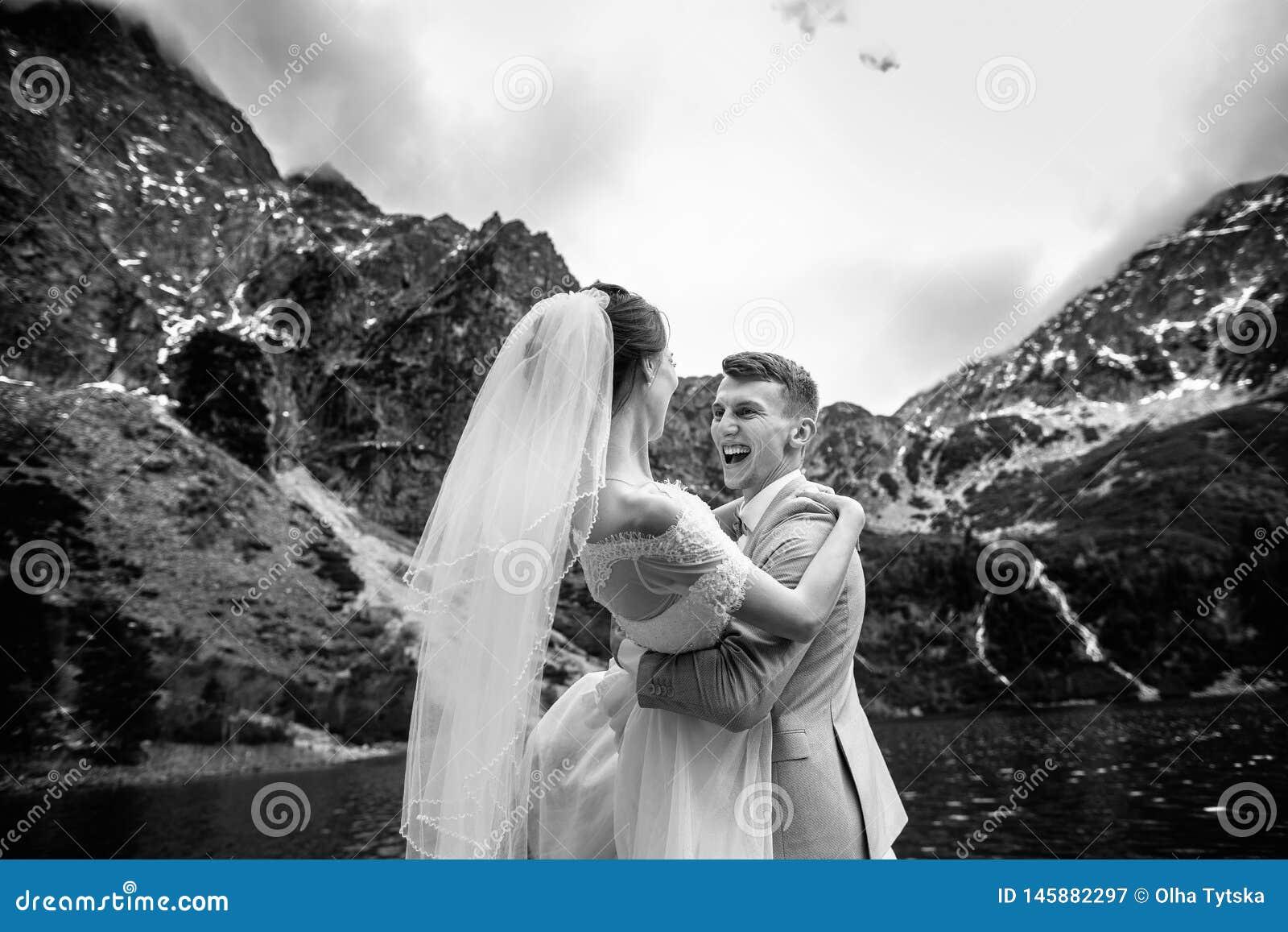 De bruidegom omcirkelt zijn jonge bruid, op de kust van het meer Morskie Oko polen De Zwart-witte foto van Peking, China