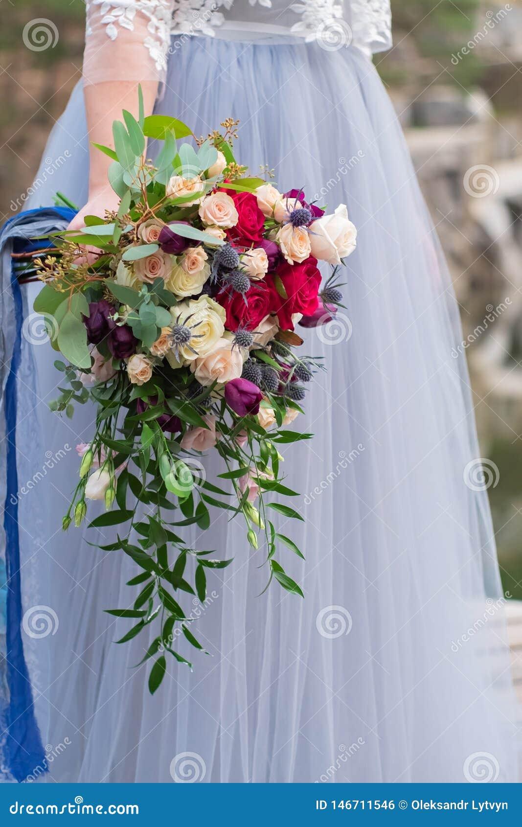 De bruidenhand houdt een huwelijksboeket van rozen en feverweed op de achtergrond van een huwelijkskleding