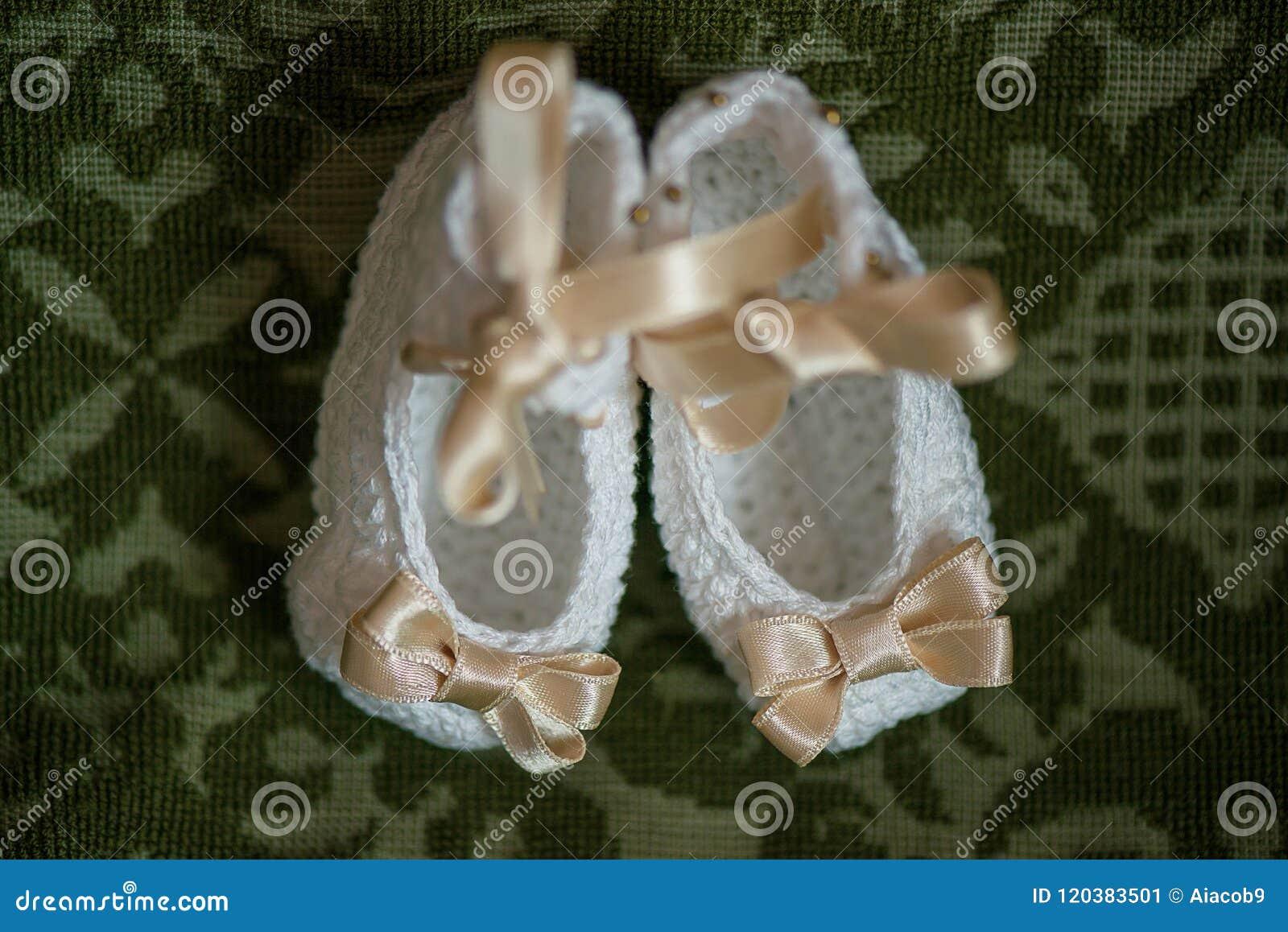 De buiten van het babymeisje in wit met beige linten