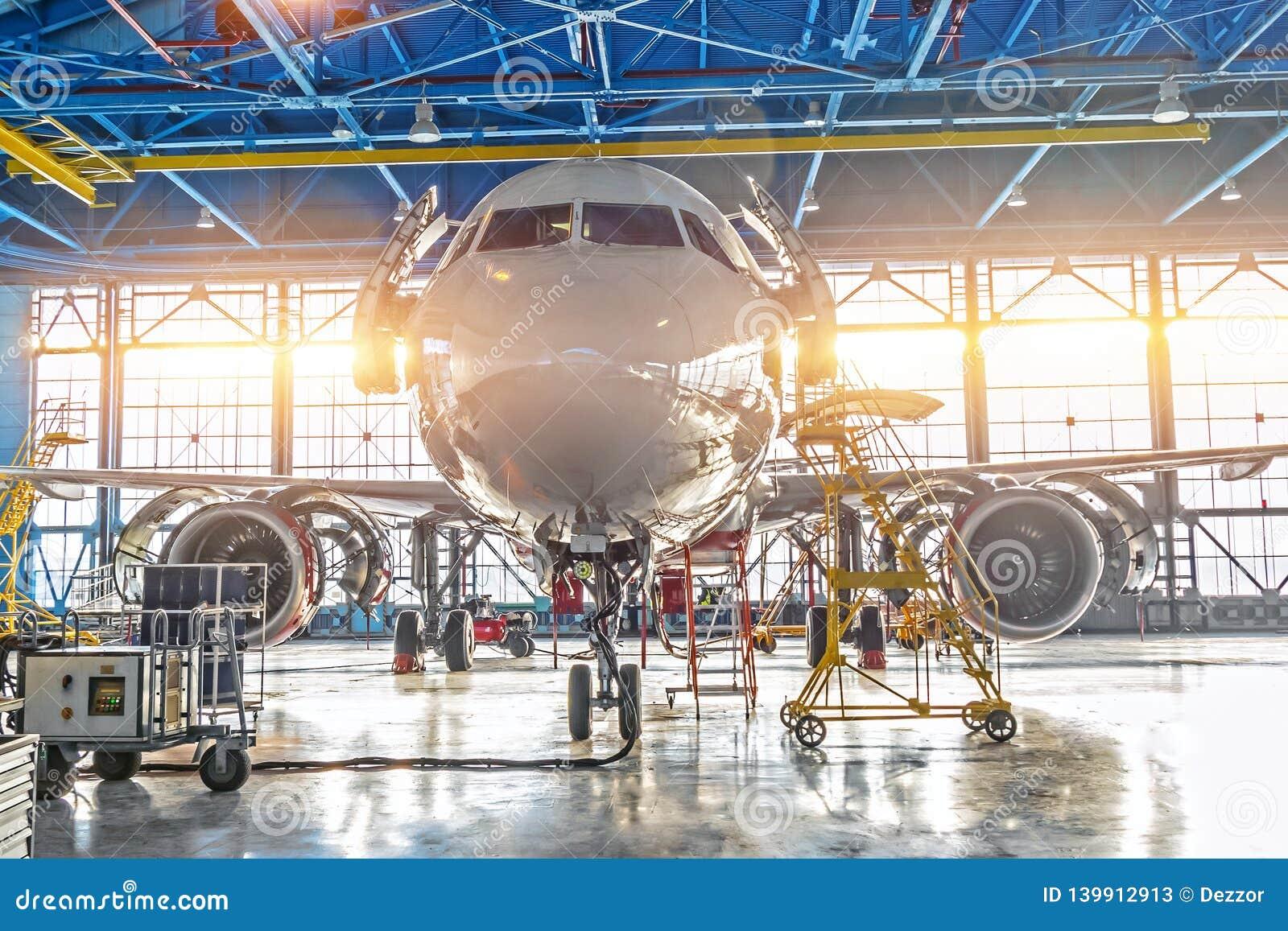 De burgerlijke vliegtuigstraal op onderhoud van motor en de fuselage controleren reparatie in luchthavenhangaar Helder licht bij