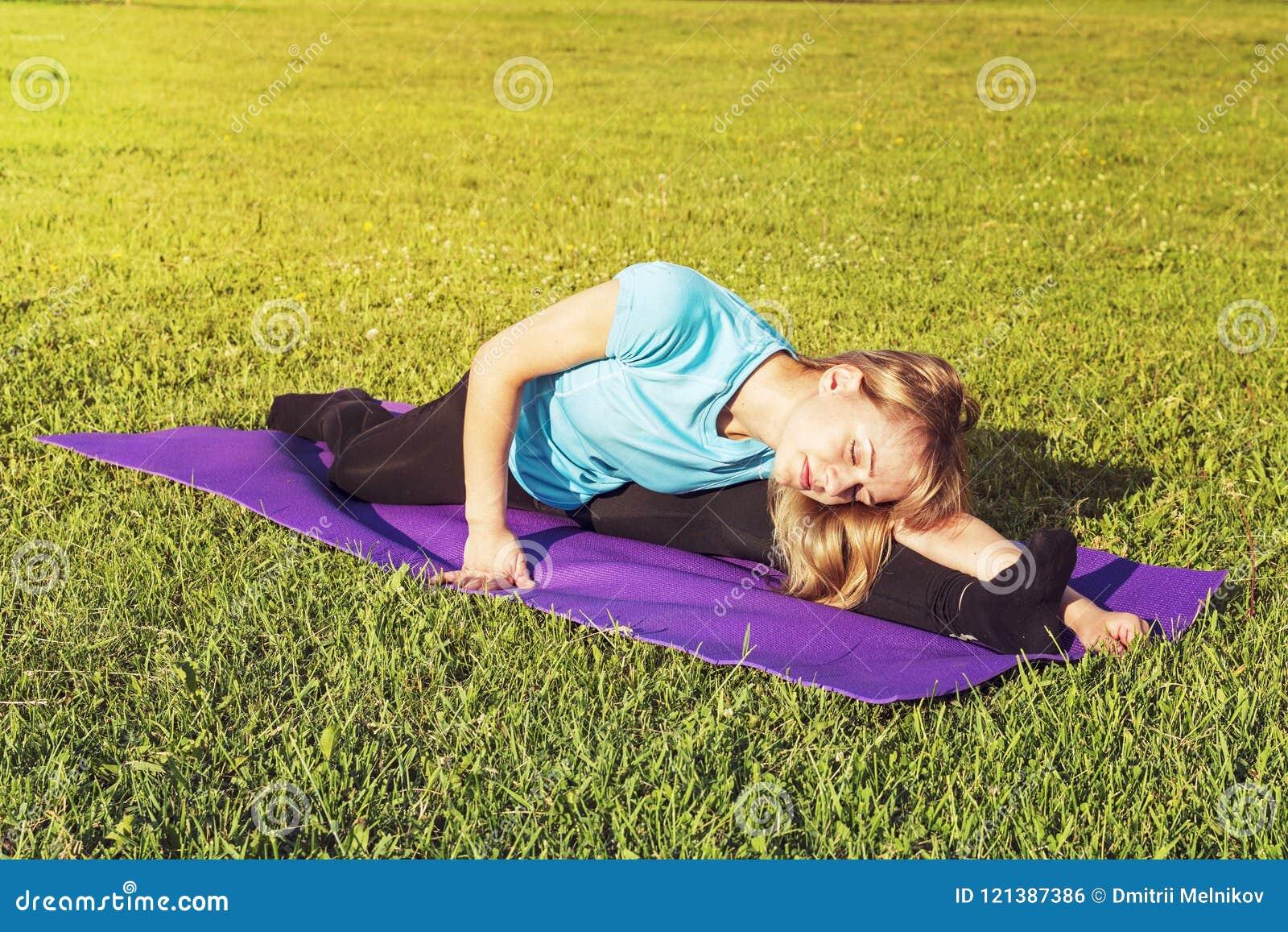 De bus van de blondevrouw in een sportieve korte bovenkant en gymnastiekbeenkappen maakt een brede streng op de deken want de yog