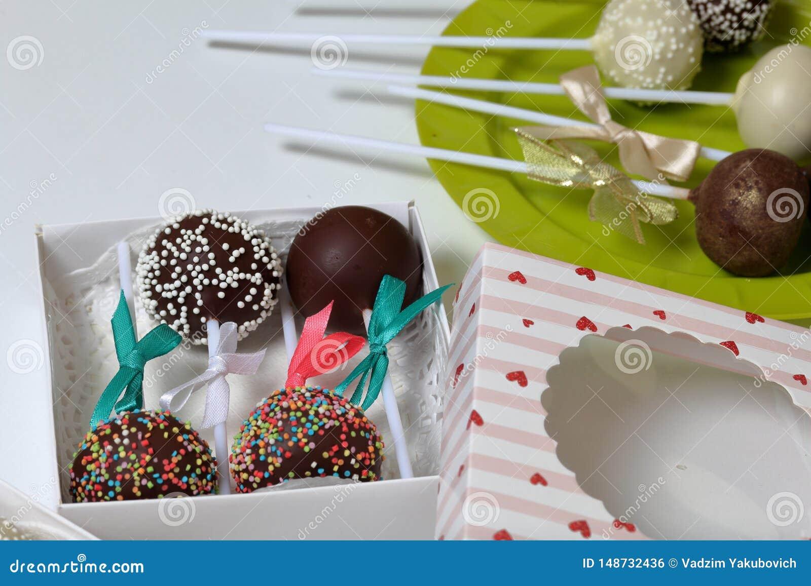 De cake knalt verfraaid met een boog van vlecht, die in een giftdoos wordt ingepakt Andere snoepjes zijn dicht langs op de plaat