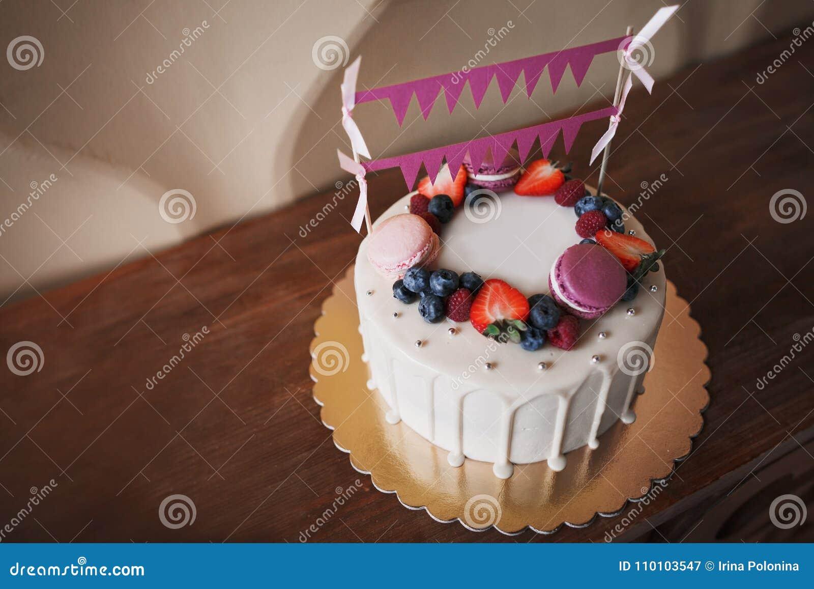 De cake van de kinderen` s verjaardag Op de cake zijn er frambozenbessen, bosbessen en aardbeien, purpere en roze makarons, decor