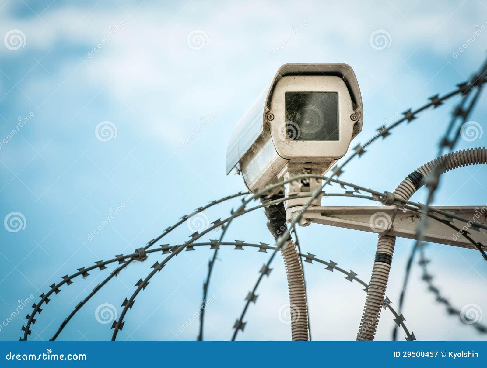 De camera van de observatie en barbwire op blauwe hemel.
