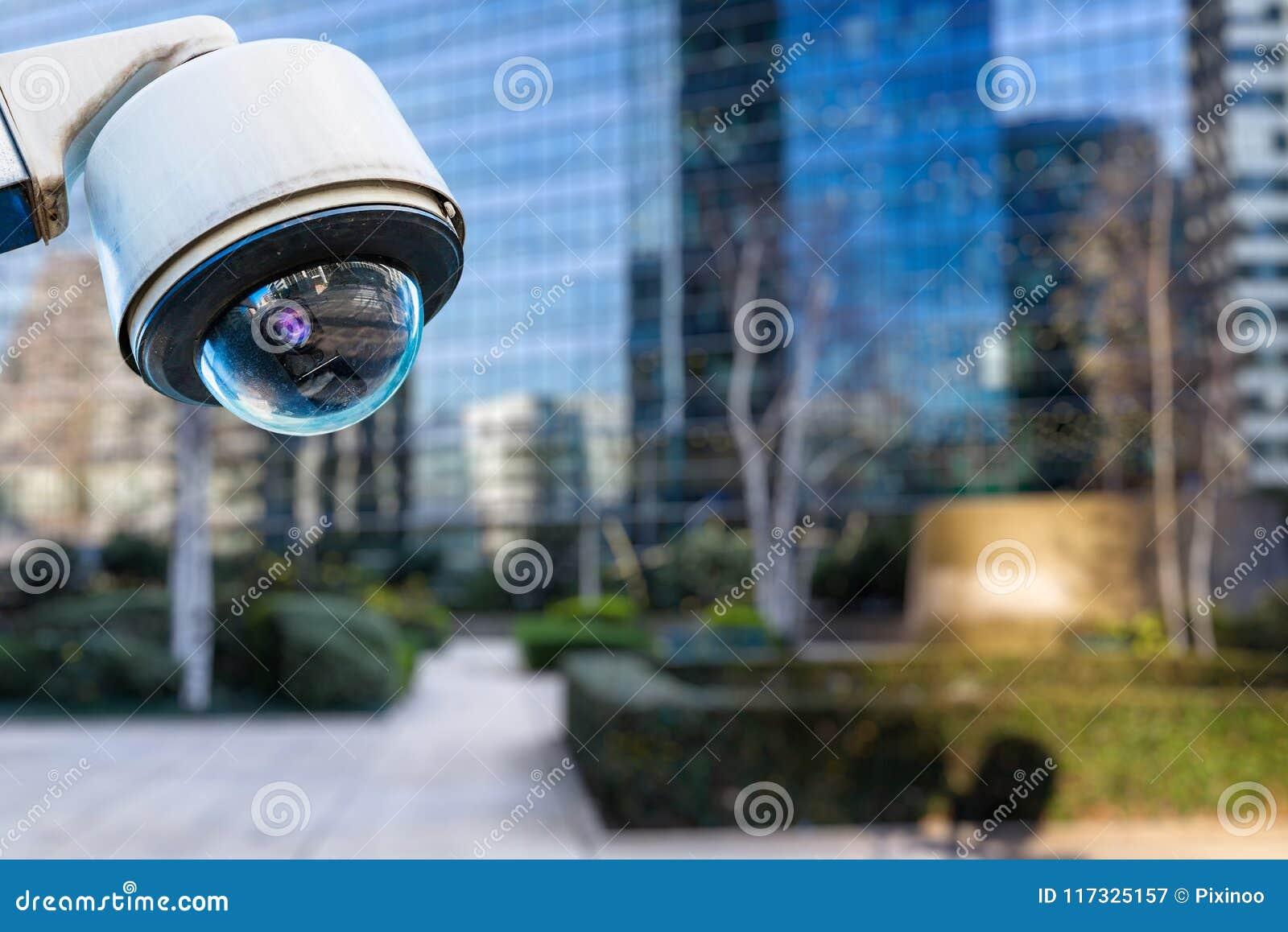 De camera van veiligheidskabeltelevisie of toezichtsysteem met gebouwen op onscherpe achtergrond