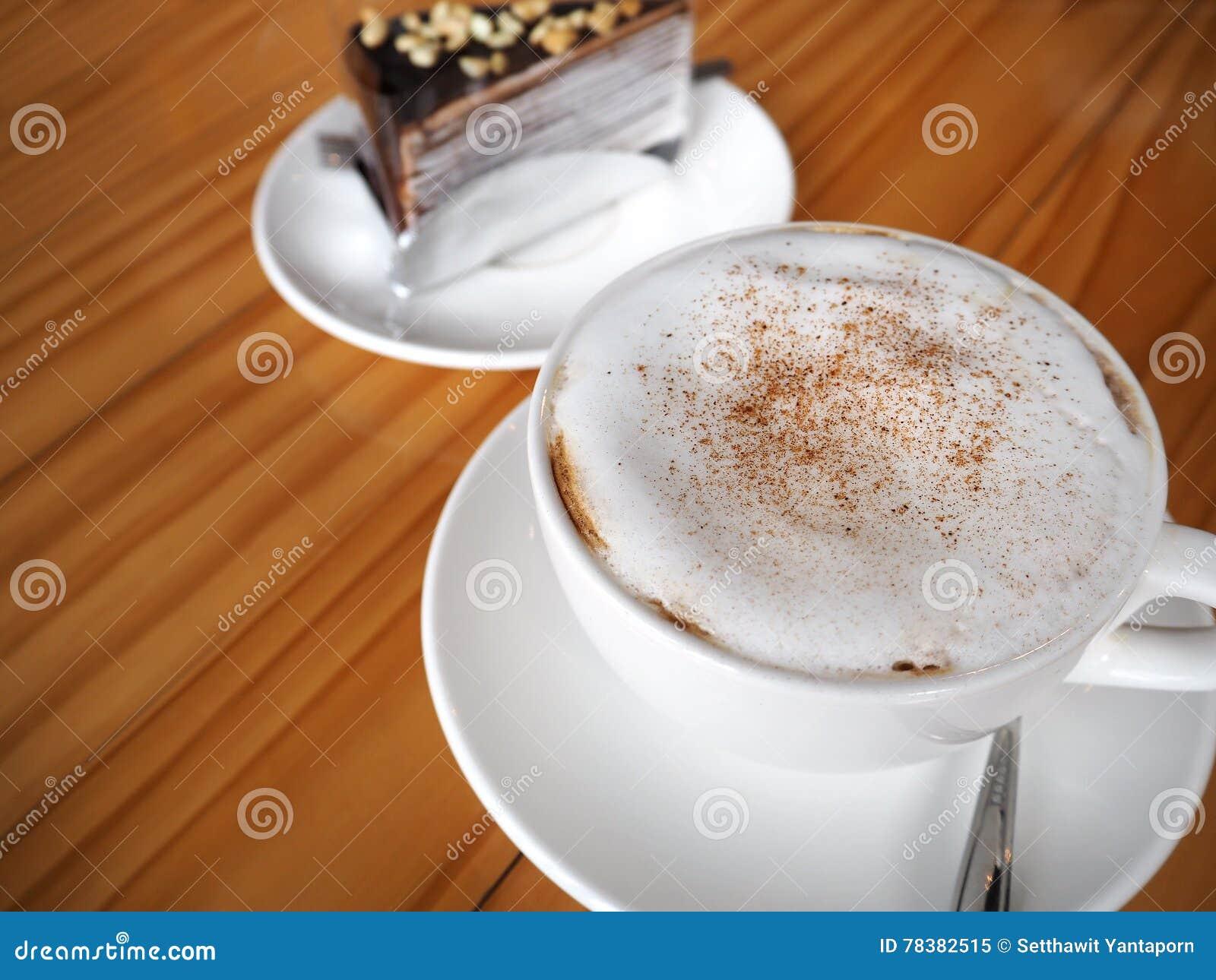 De cappuccinokoffie in witte kop met chocolade omfloerst cake op hout