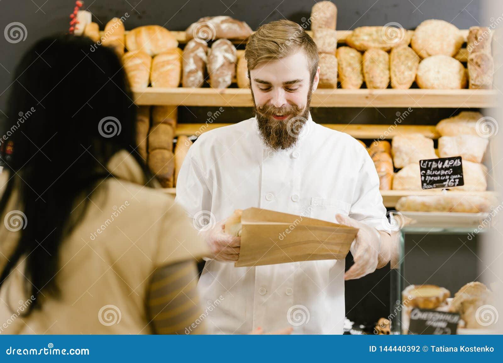 De charismatische bakker met een baard en een snor geeft een document zak brood aan de klant in de bakkerij