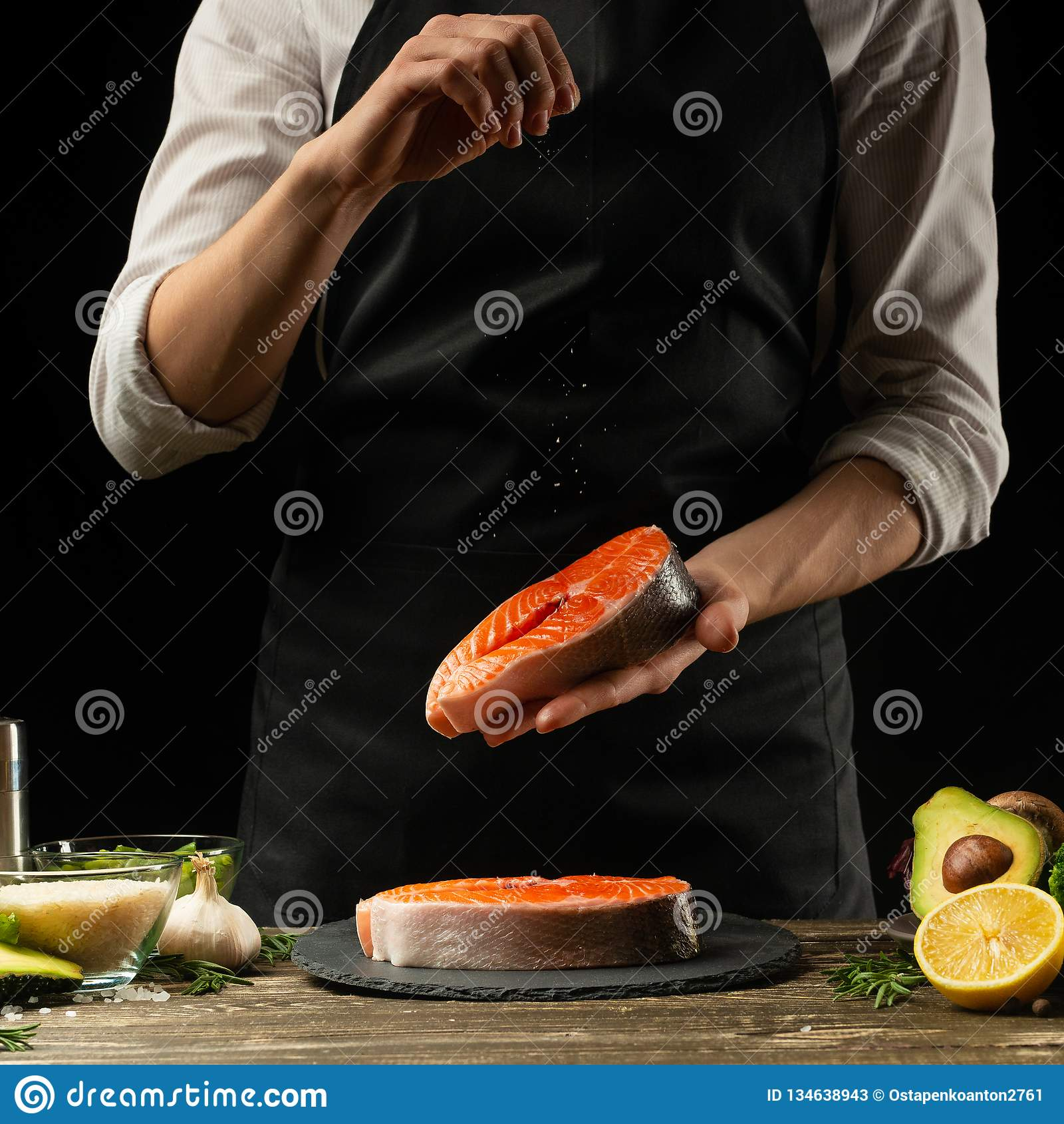 De chef-kok bereidt verse zalmvissen, Crumbu-forel voor, bestrooit overzees zout met ingrediënten Het voorbereiden van vissenvoed