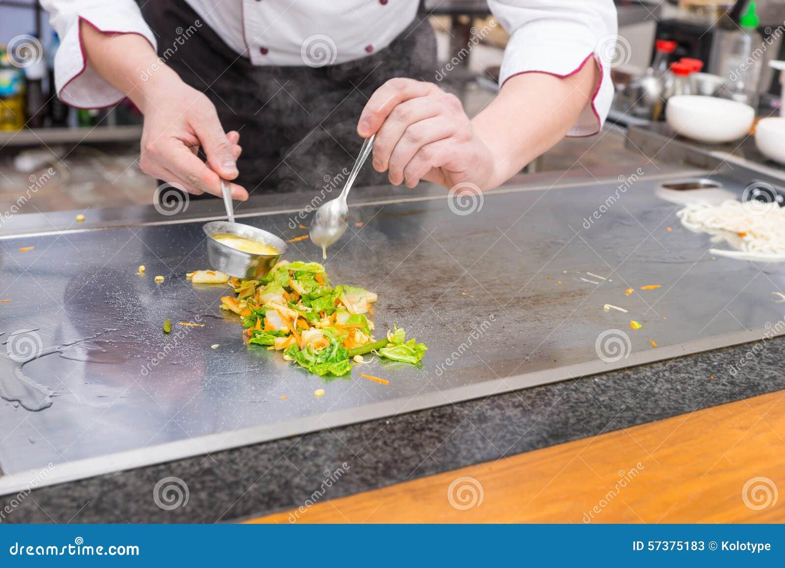 De chef-kok die verse groente voorbereiden beweegt gebraden gerecht