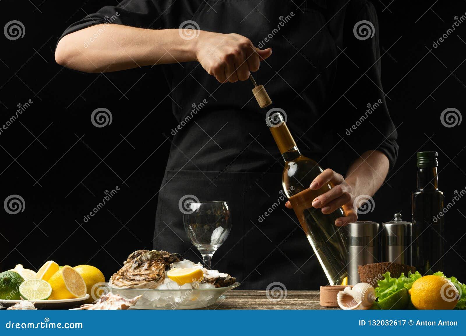 De chef-kok opent Italiaanse droge wijn met oesters met citroen, op een donkere achtergrond