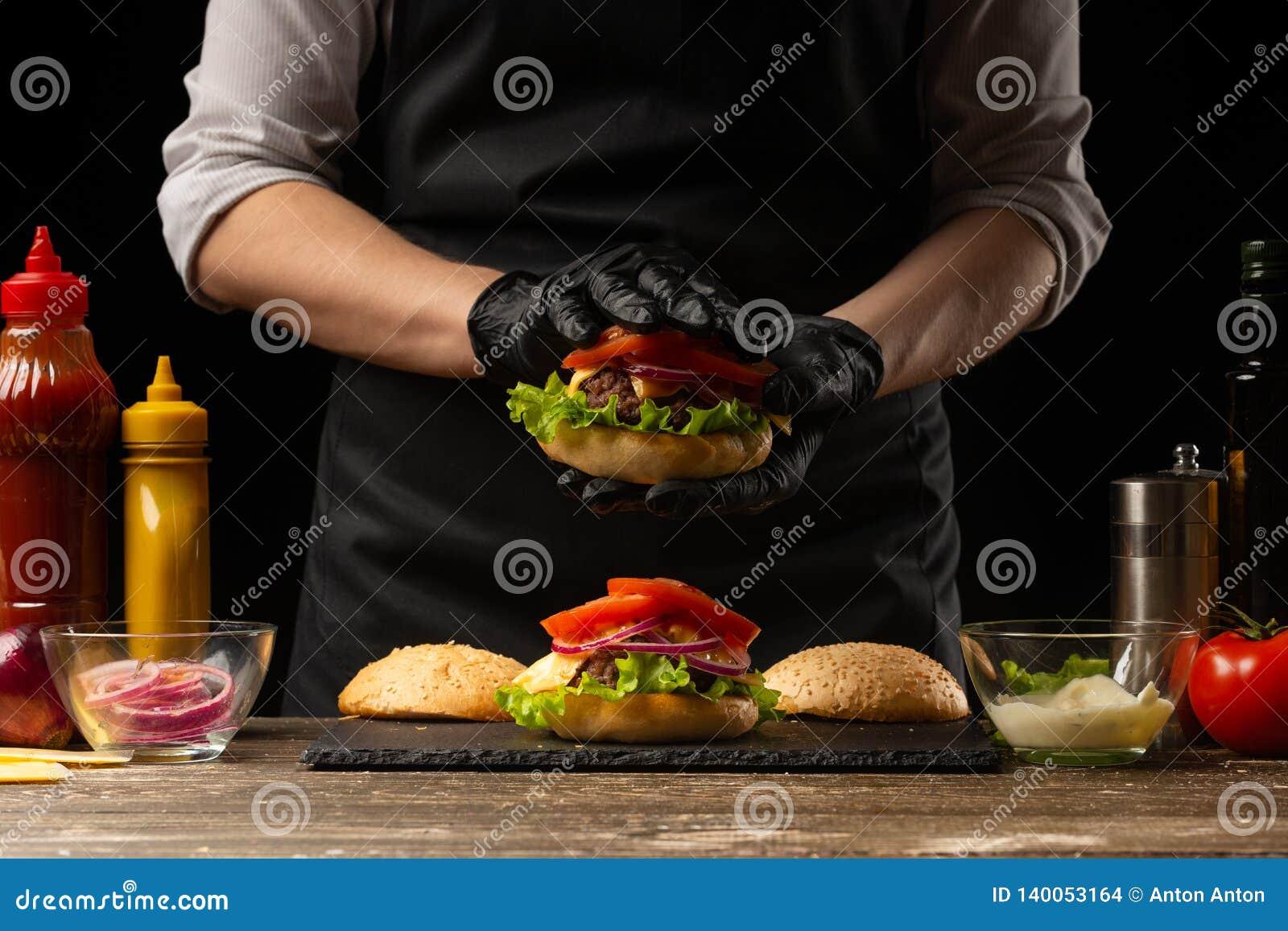 De chef-kok zet tomatenringen op een hamburger, op de achtergrond van de ingrediënten Horizontale foto, Smakelijk en ongezond voe