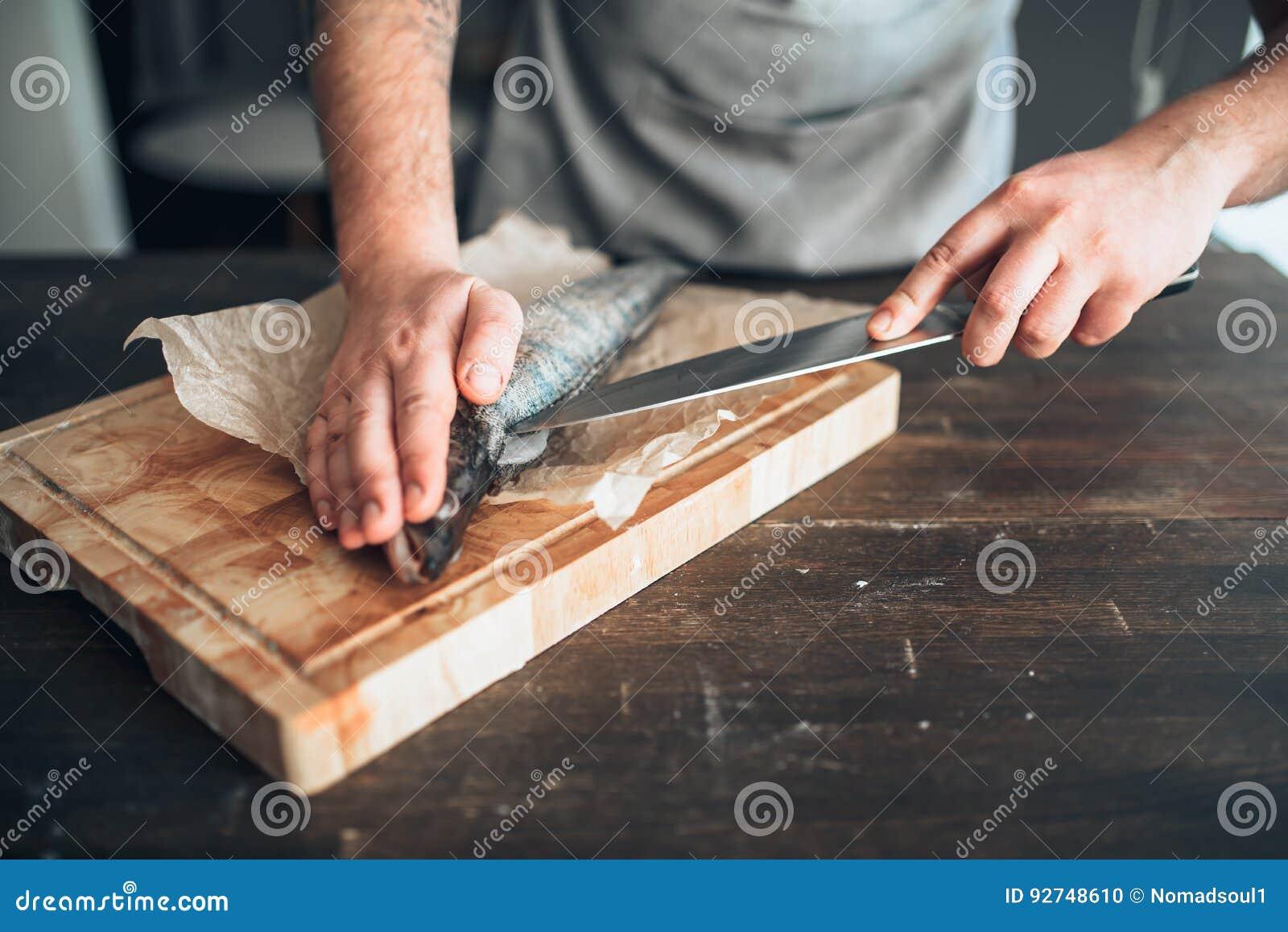 De chef-kokhanden met mes snijden omhoog vissen op scherpe raad