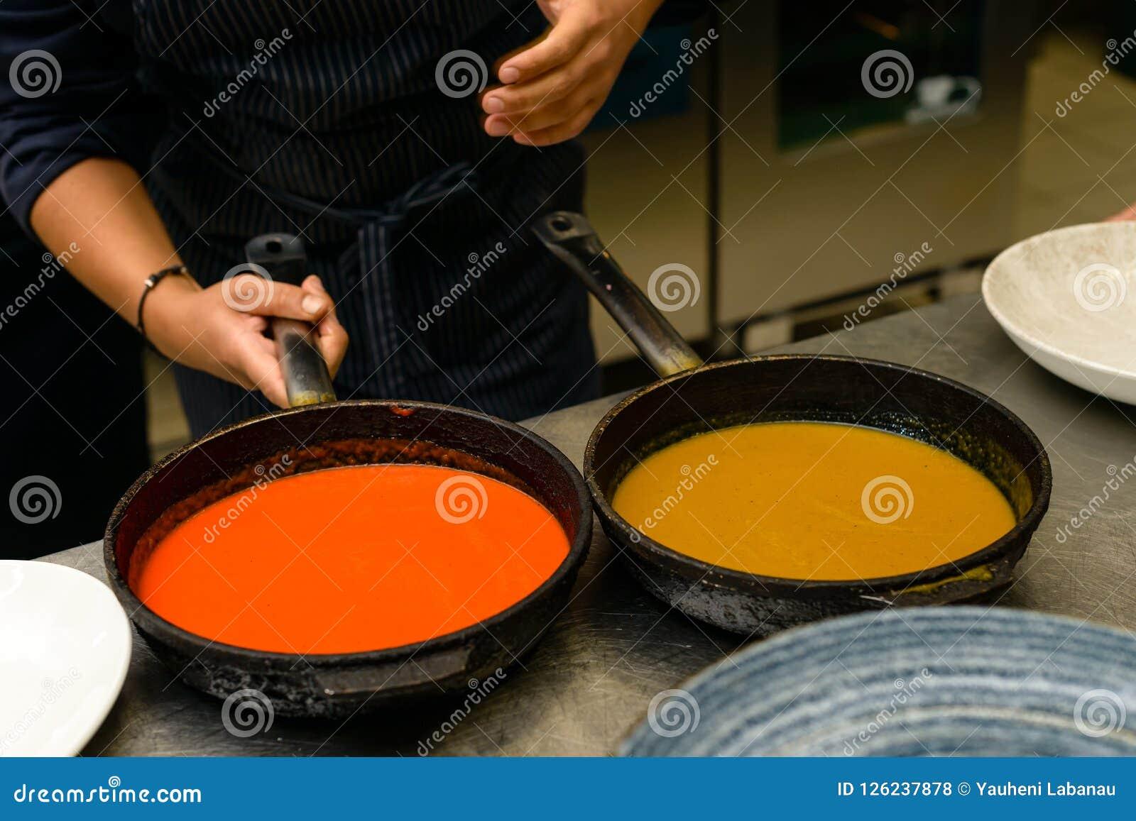 De chef-kokkok bereidt een hete saus in pan voor een heerlijke maaltijd in keukenrestaurant voor