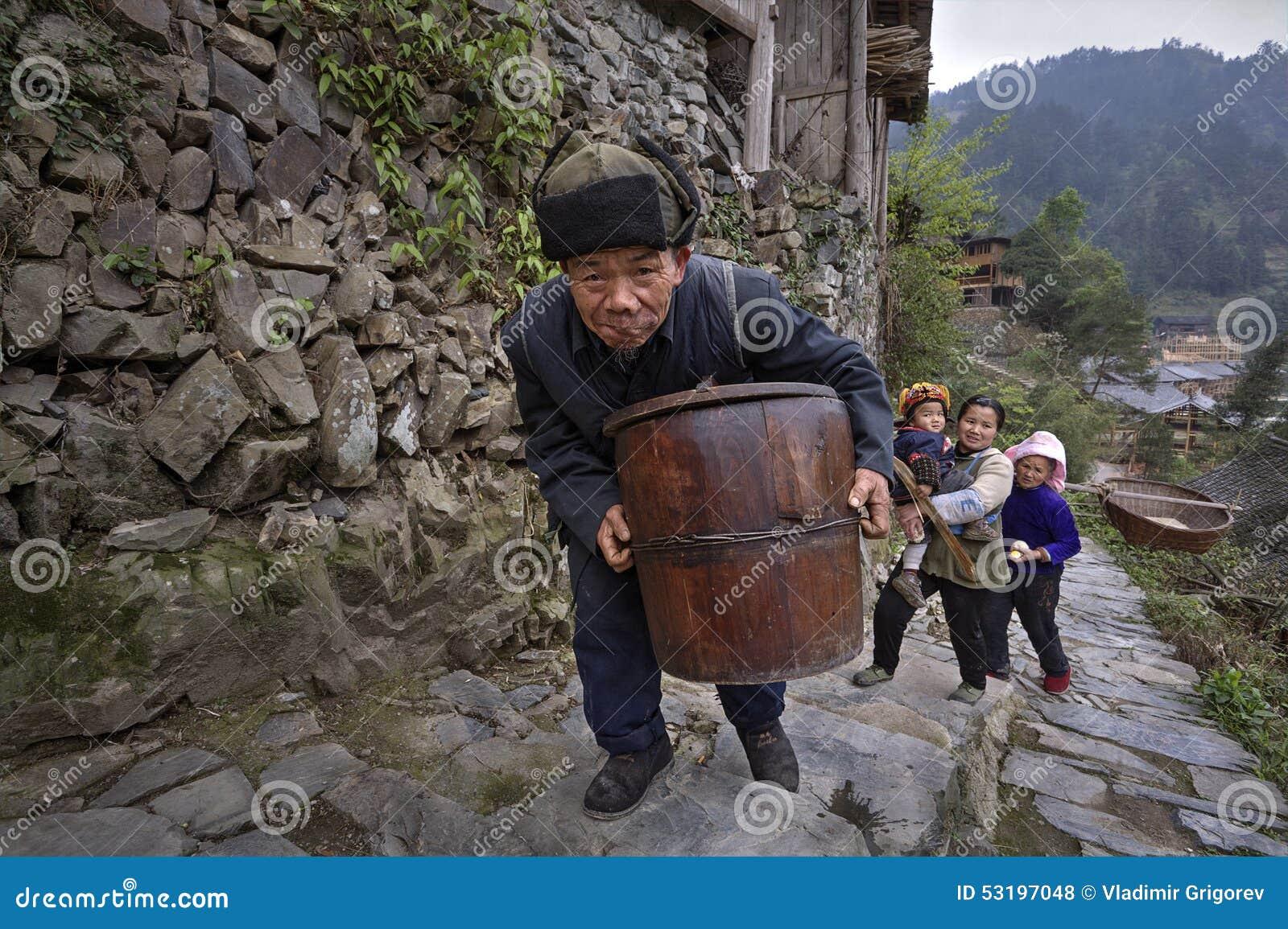 De Chinese oudere mens beklimt de weg van de steenberg met houten vat