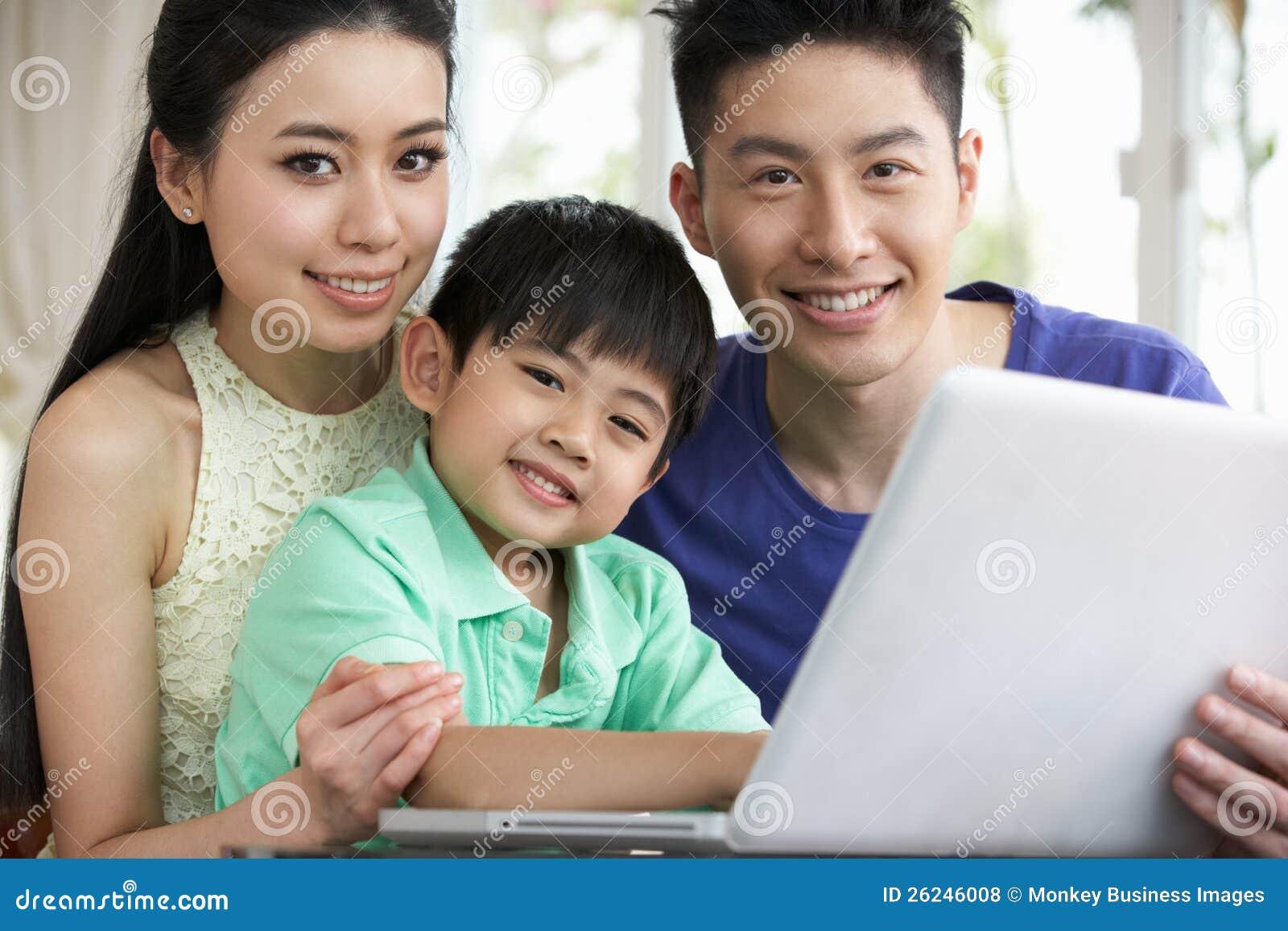 De Chinese Zitting die van de Familie Laptop thuis met behulp van