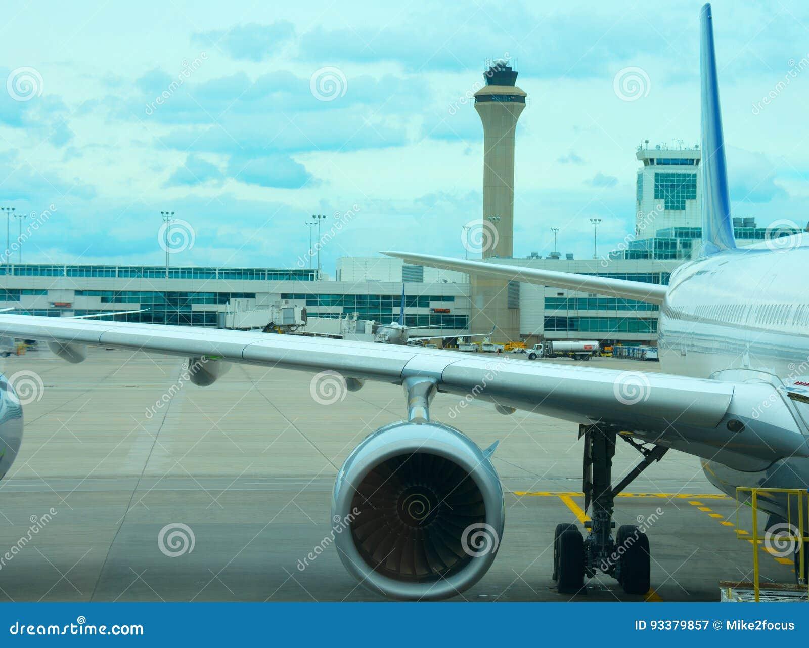 De close-up van het lijnvliegtuigvliegtuig op tarmac met de toren van de luchtverkeerscontrole op achtergrond