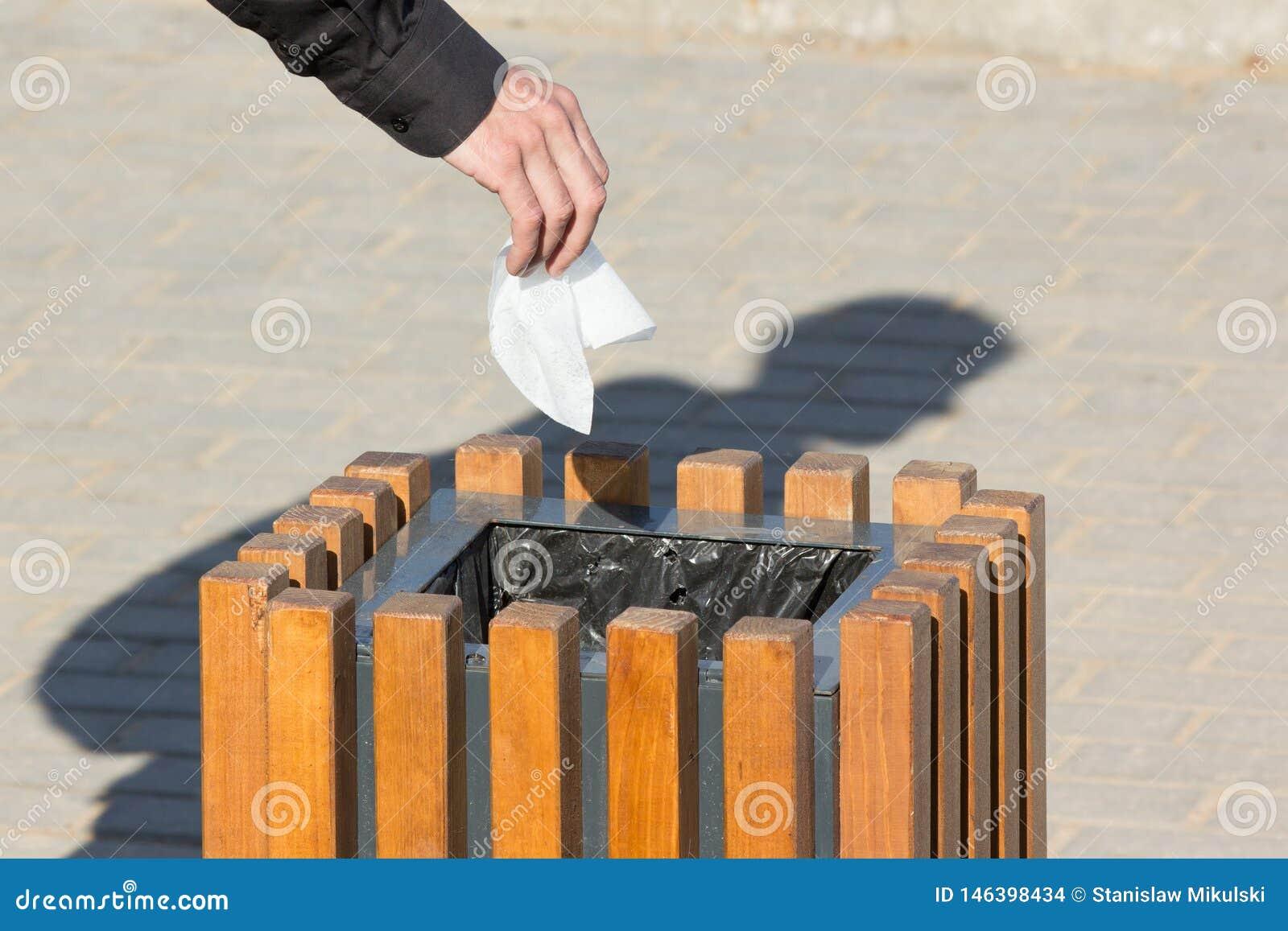 De close-uphand laat vallen stuk van huisvuil in vuilnisbak