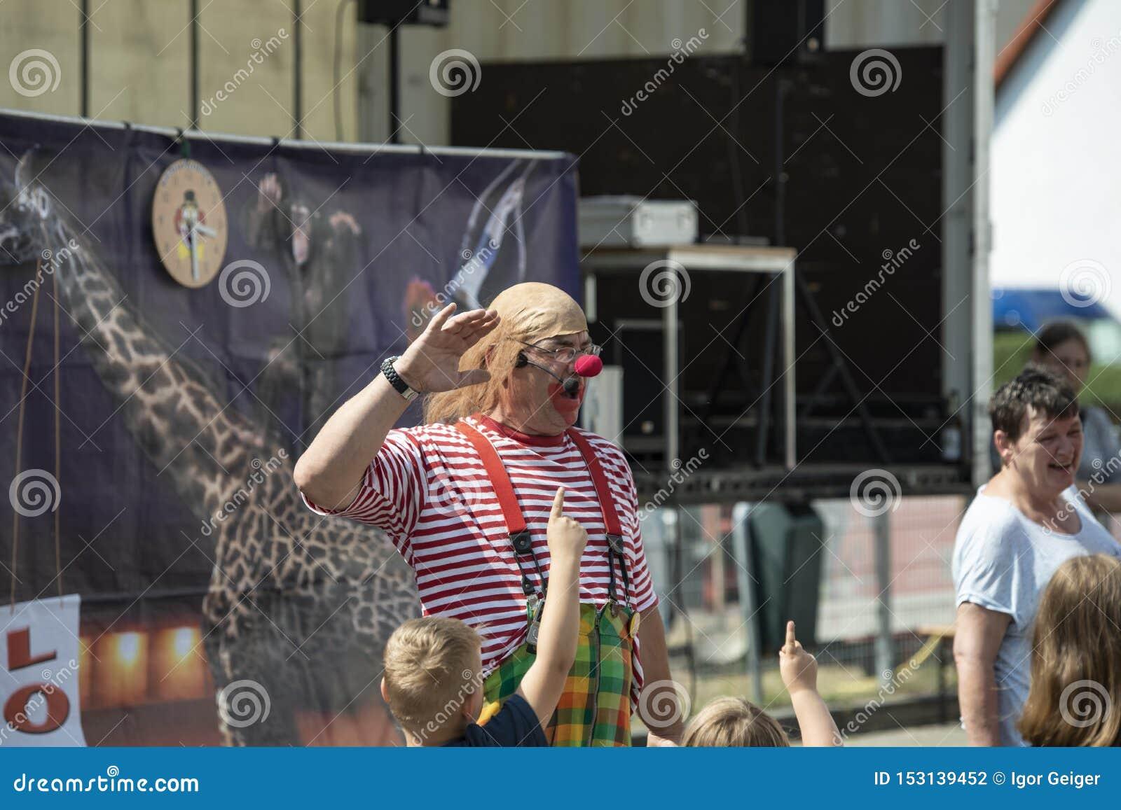 De clownanimator onderhoudt kinderen bij een brandfestival in de stad van Halle Saale, Duitsland, 2019