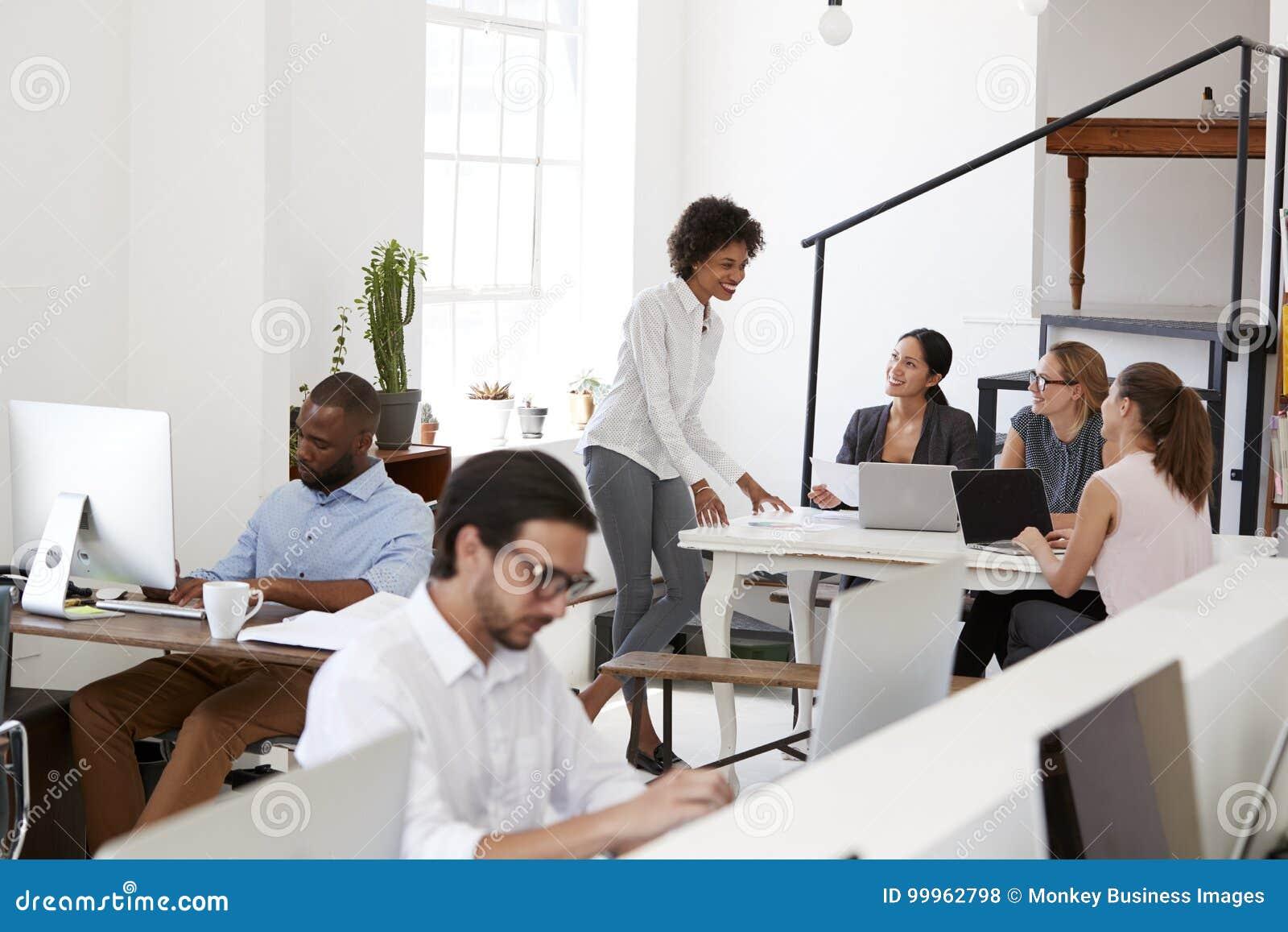 De collega s van de vrouwenbriefing rond een bureau in open planbureau