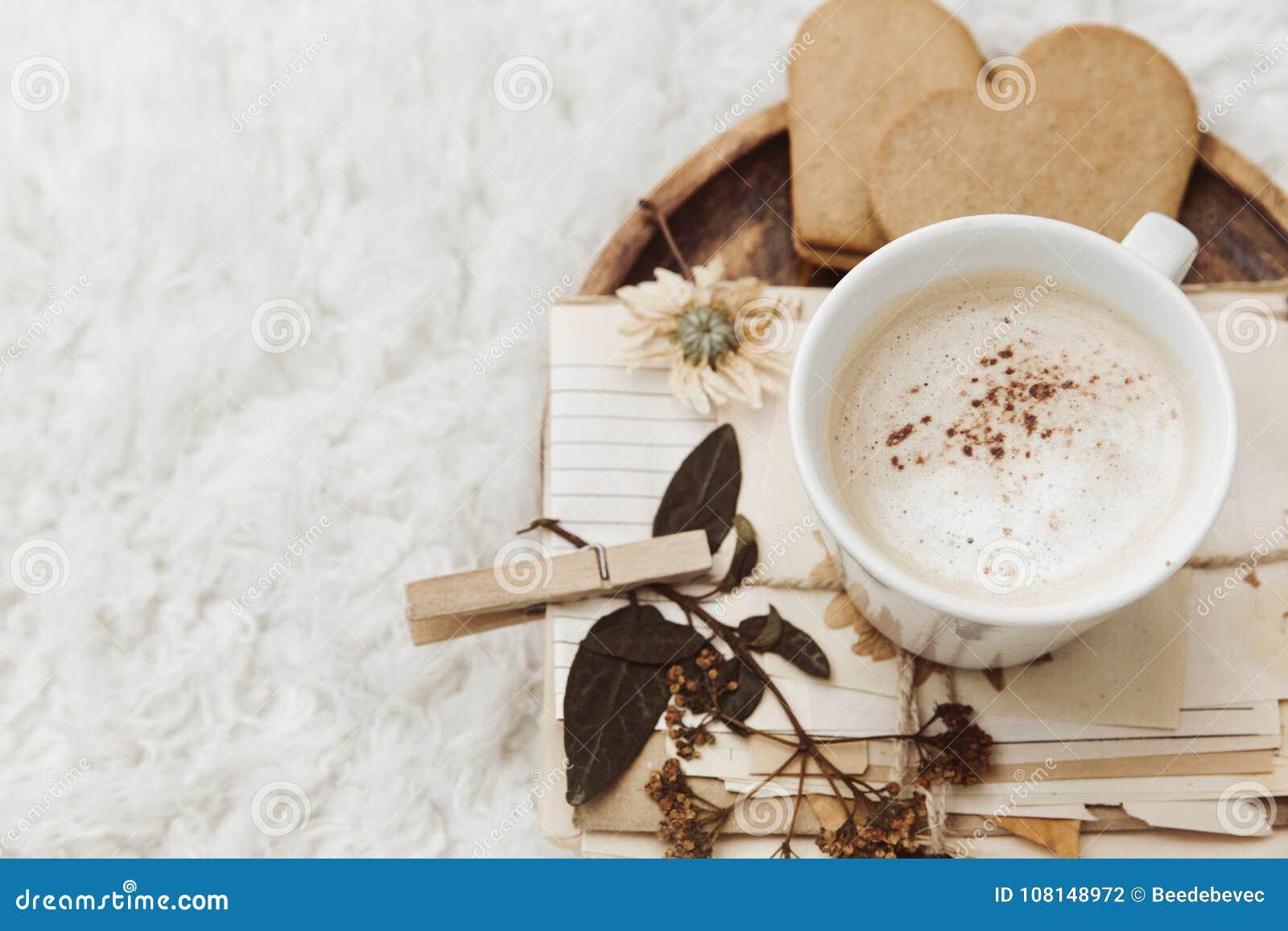 De comfortabele achtergrond van het de winterhuis, kop van koffie, oud uitstekend document op witte achtergrond