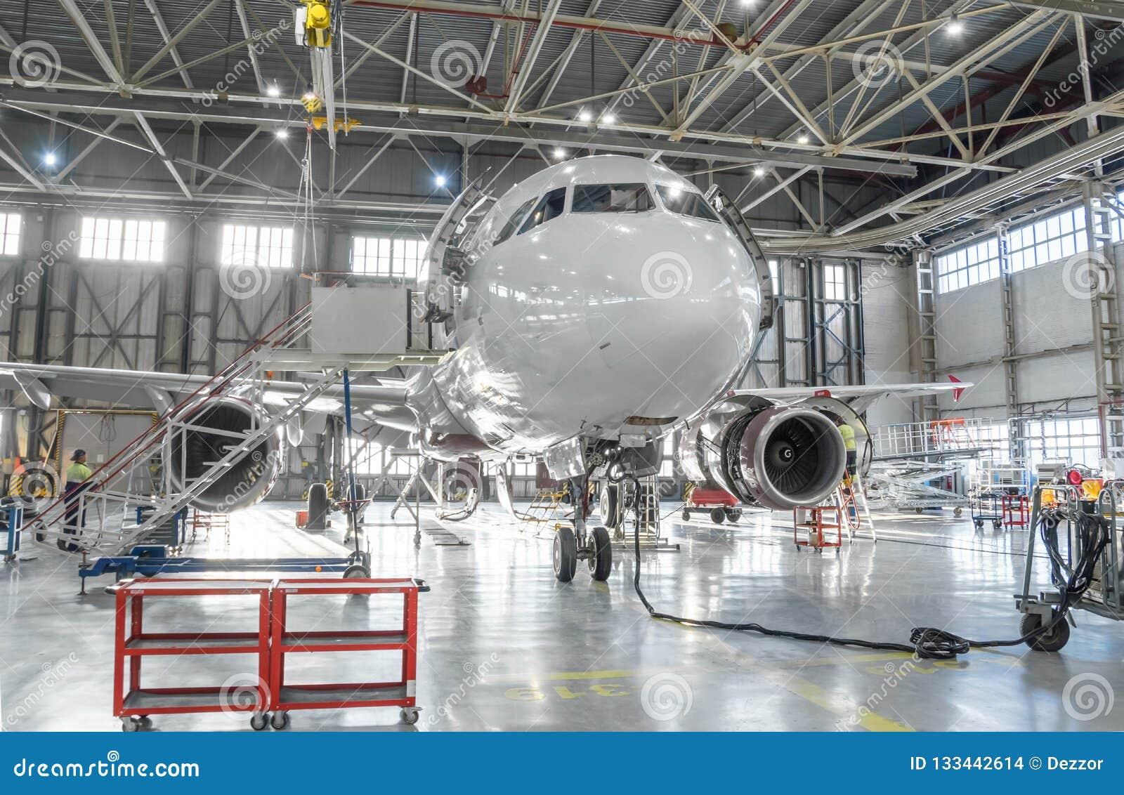 De commerciële vliegtuigenstraal op onderhoud van motor en de fuselage controleren reparatie in luchthavenhangaar