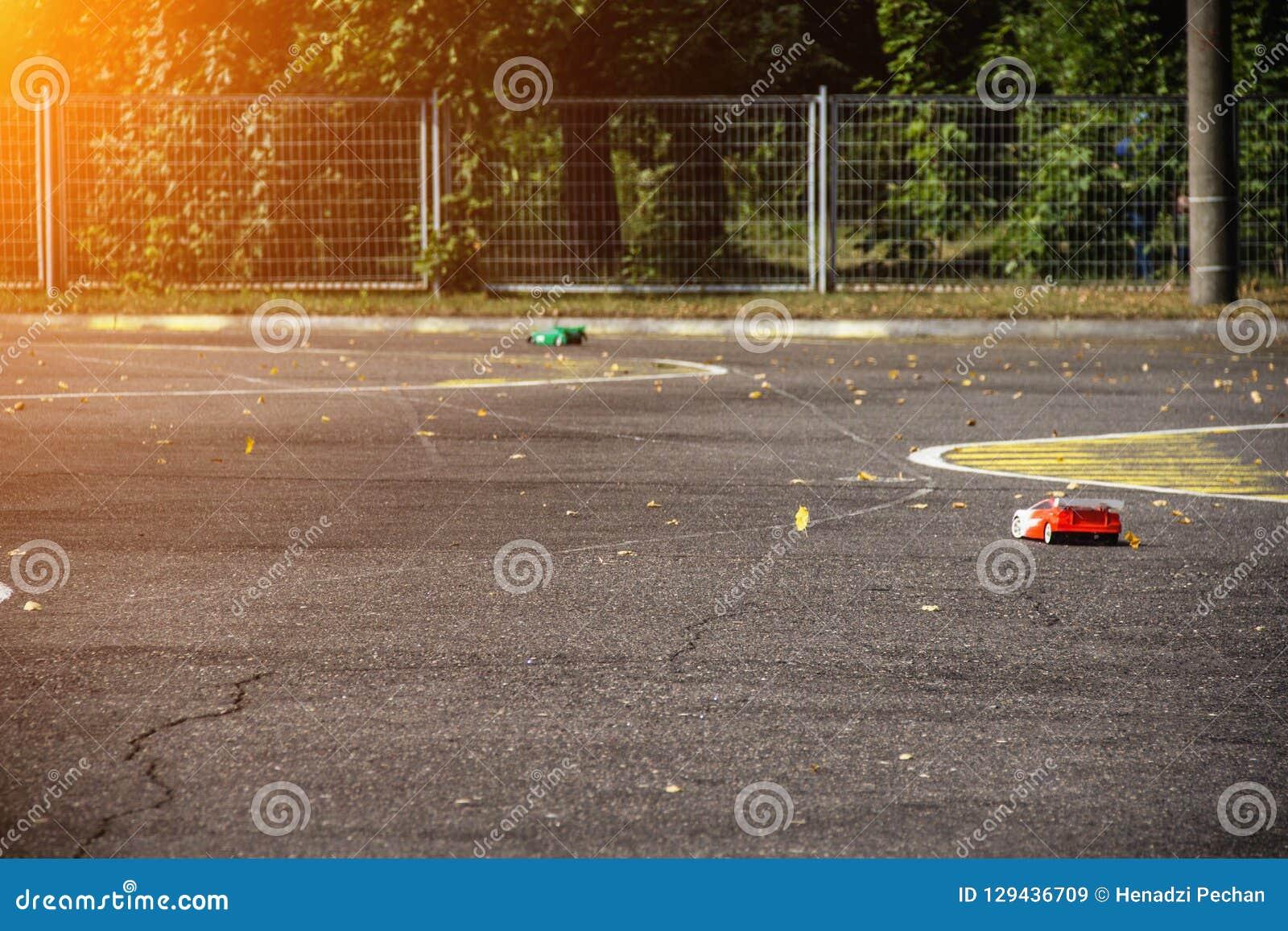 De competities op autosport op de radio, twee auto s op de radio gaan op een asfaltweg, de zon, snelheid