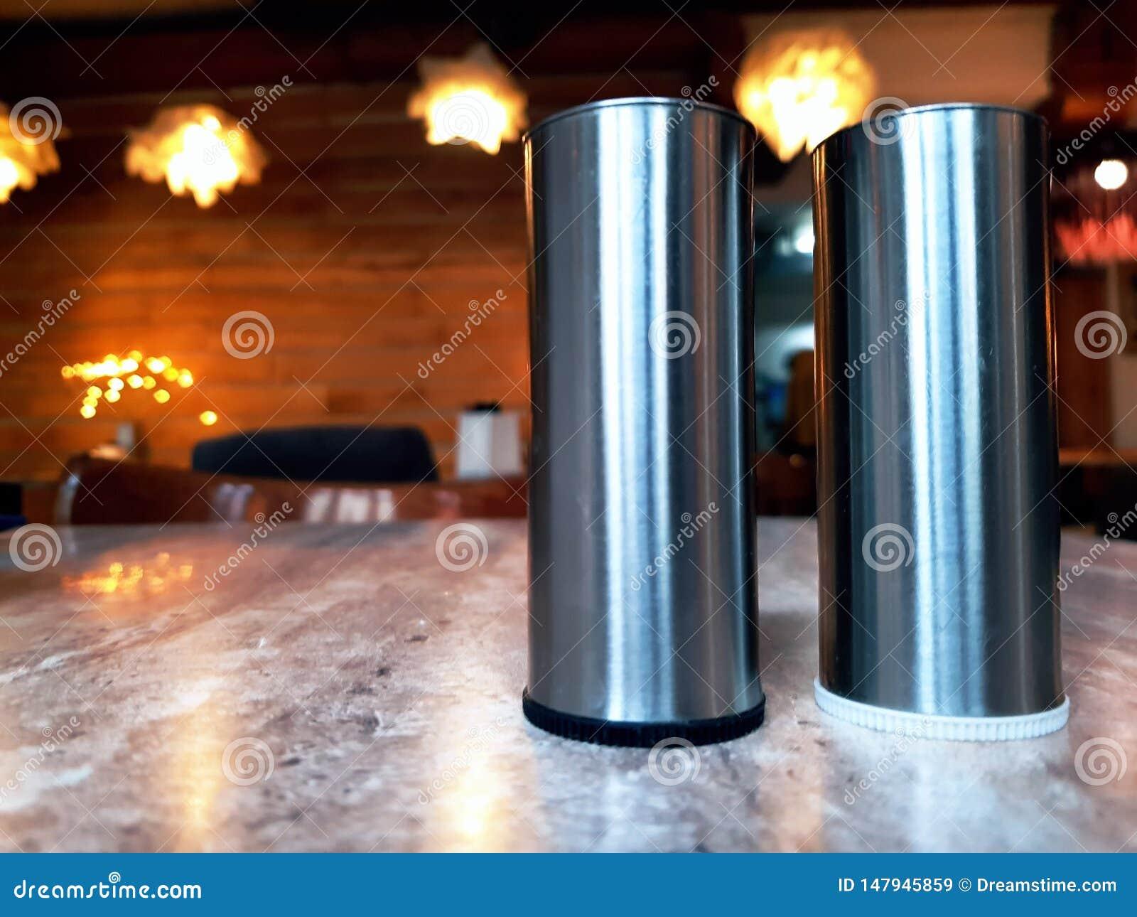 De containers van het kruidmetaal op een witte oppervlakte Kruidkruiken Keukenmateriaal op de lijst, onscherpe achtergrond Keuken